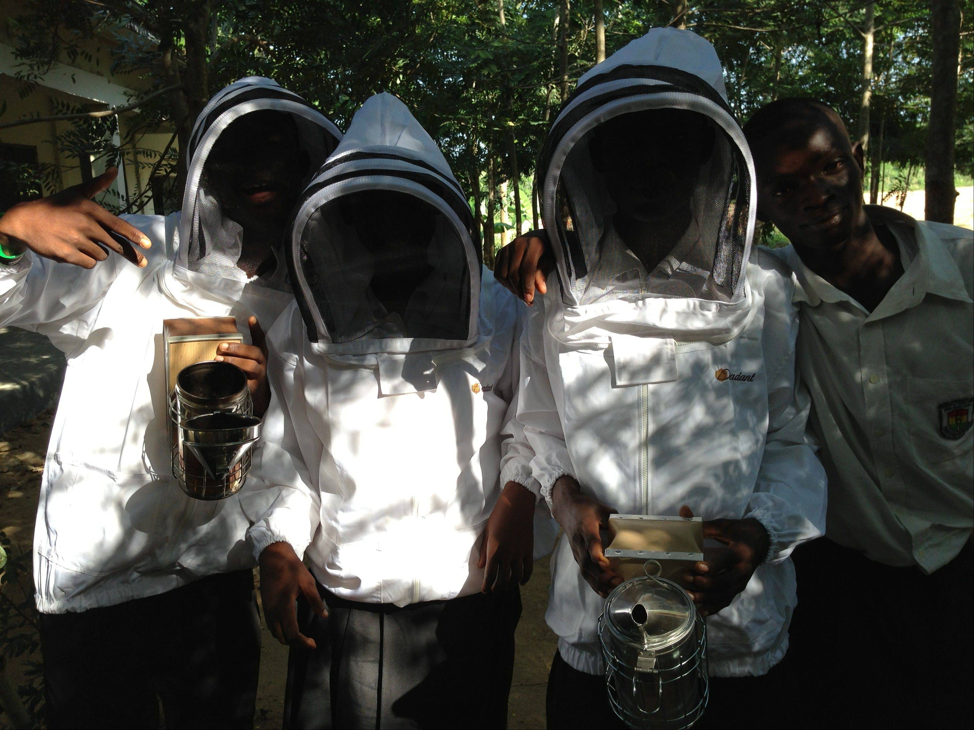 Students at high school in Ghana show off the three bee suits sent to them by the Cantigny Golf Bee Barometer Project.