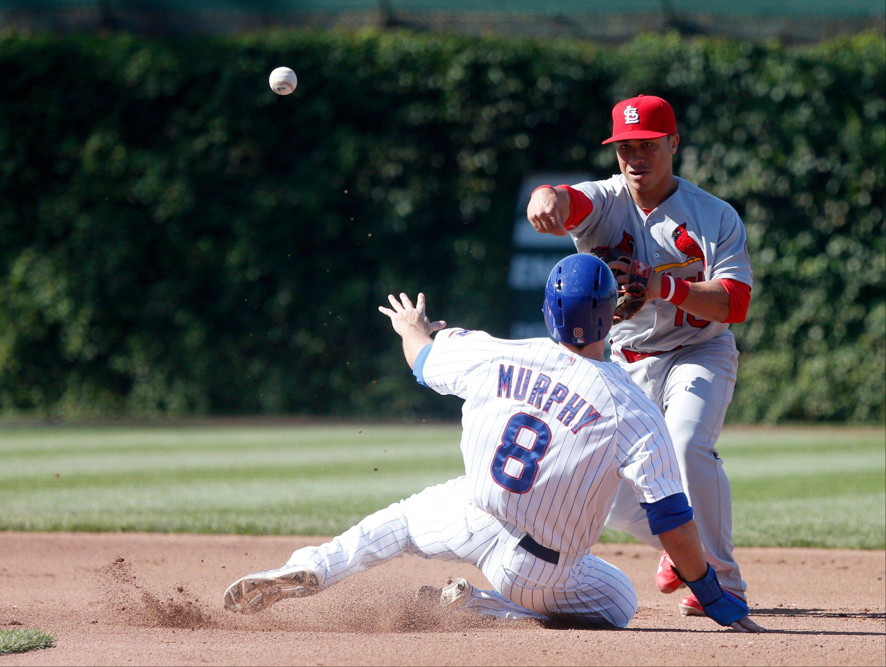 St. Louis Cardinals second baseman Kolten Wong, right, turns the double play forcing out Chicago Cubs' Donnie Murphy (8) at second and getting Starlin Castro at first during the fourth inning of a baseball game on Friday, Aug. 16, 2013, in Chicago.