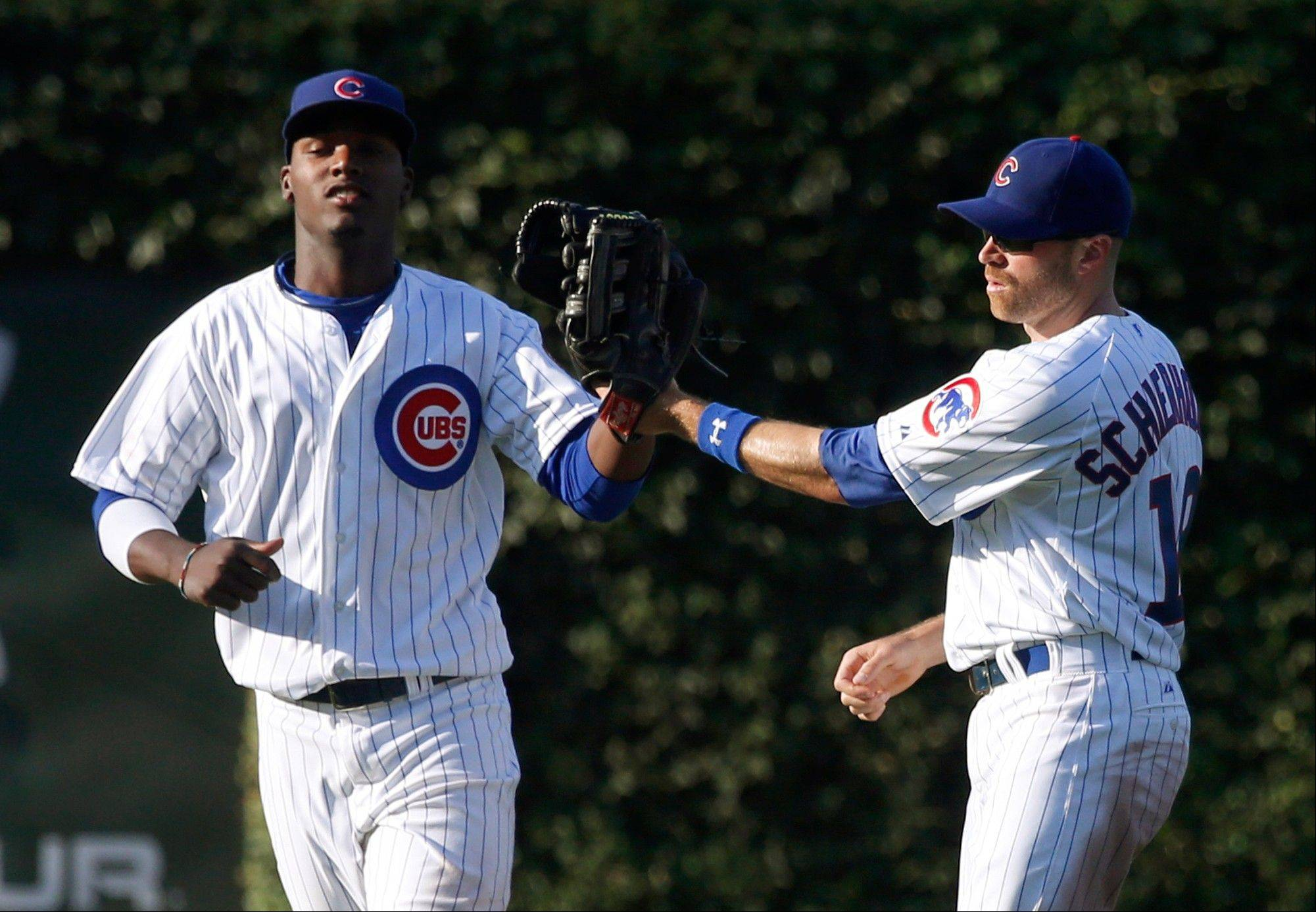 Cubs left fielder Junior Lake, left, and right fielder Nate Schierholtz celebrate the Cubs' 7-0 win over the St. Louis Cardinals in a baseball game Friday, Aug. 16, 2013, in Chicago.