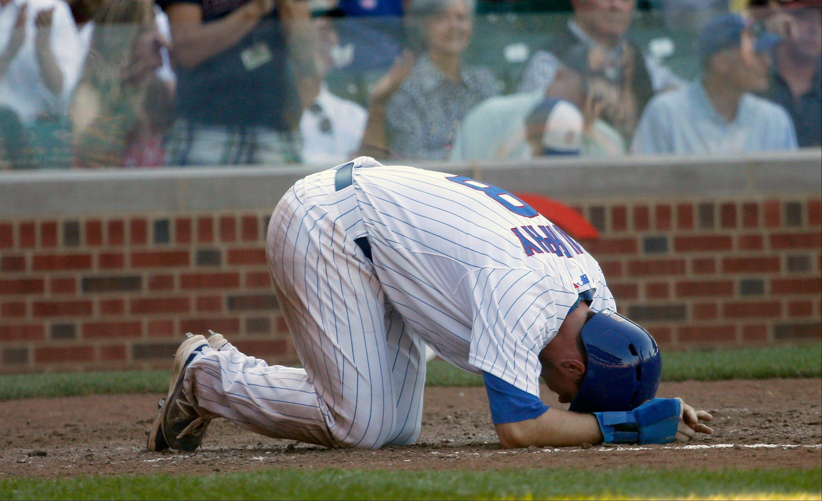 Chicago Cubs' Donnie Murphy bends over at home after scoring past St. Louis Cardinals catcher Rob Johnson on a Darwin Barney double during the sixth inning of a baseball game on Friday, Aug. 16, 2013, in Chicago.
