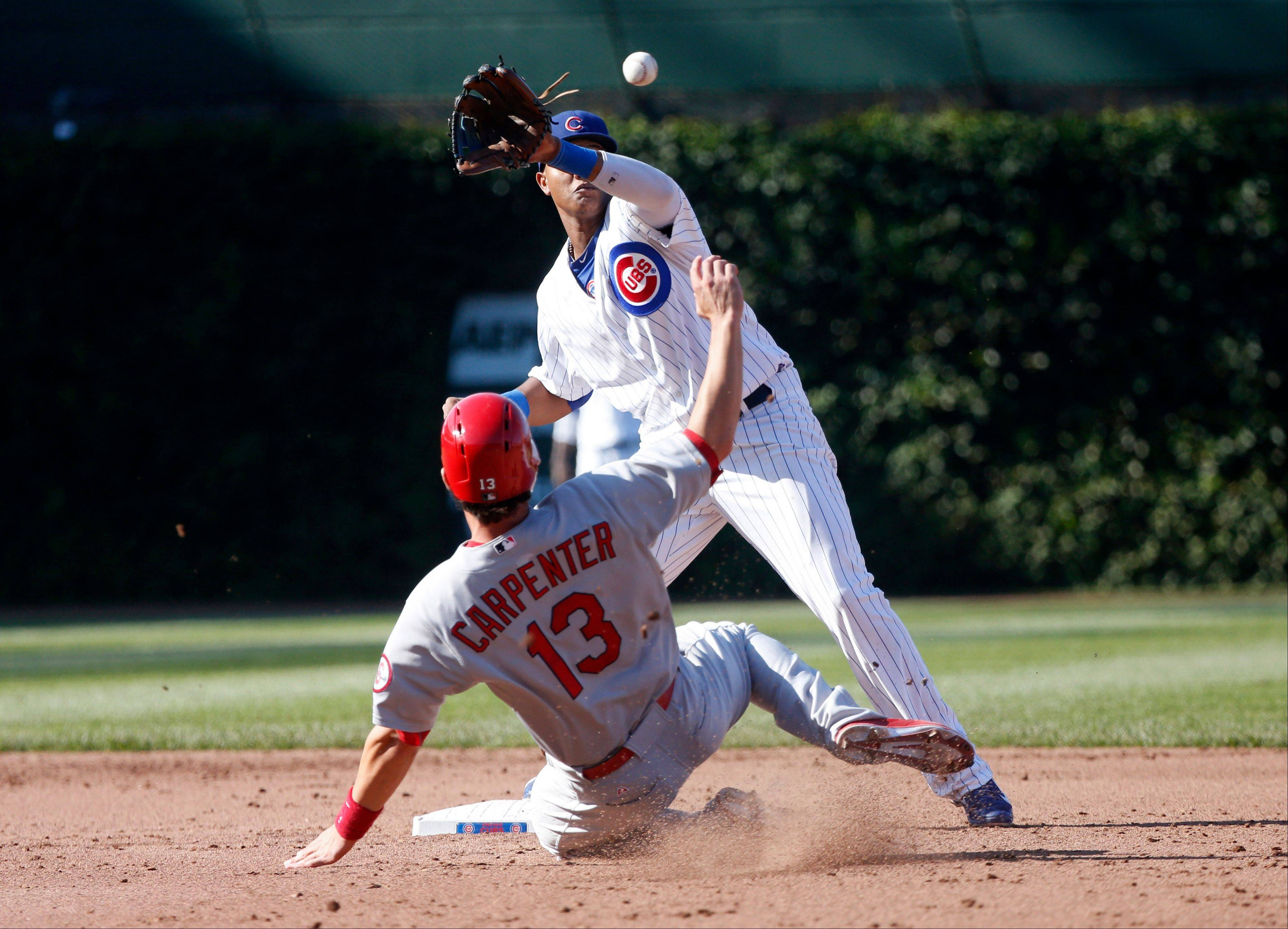 Chicago Cubs shortstop Starlin Castro, top, takes a high throw from second baseman Darwin Barney and forces out St. Louis Cardinals' Matt Carpenter (13) out at second during the sixth inning of a baseball game on Friday, Aug. 16, 2013, in Chicago.