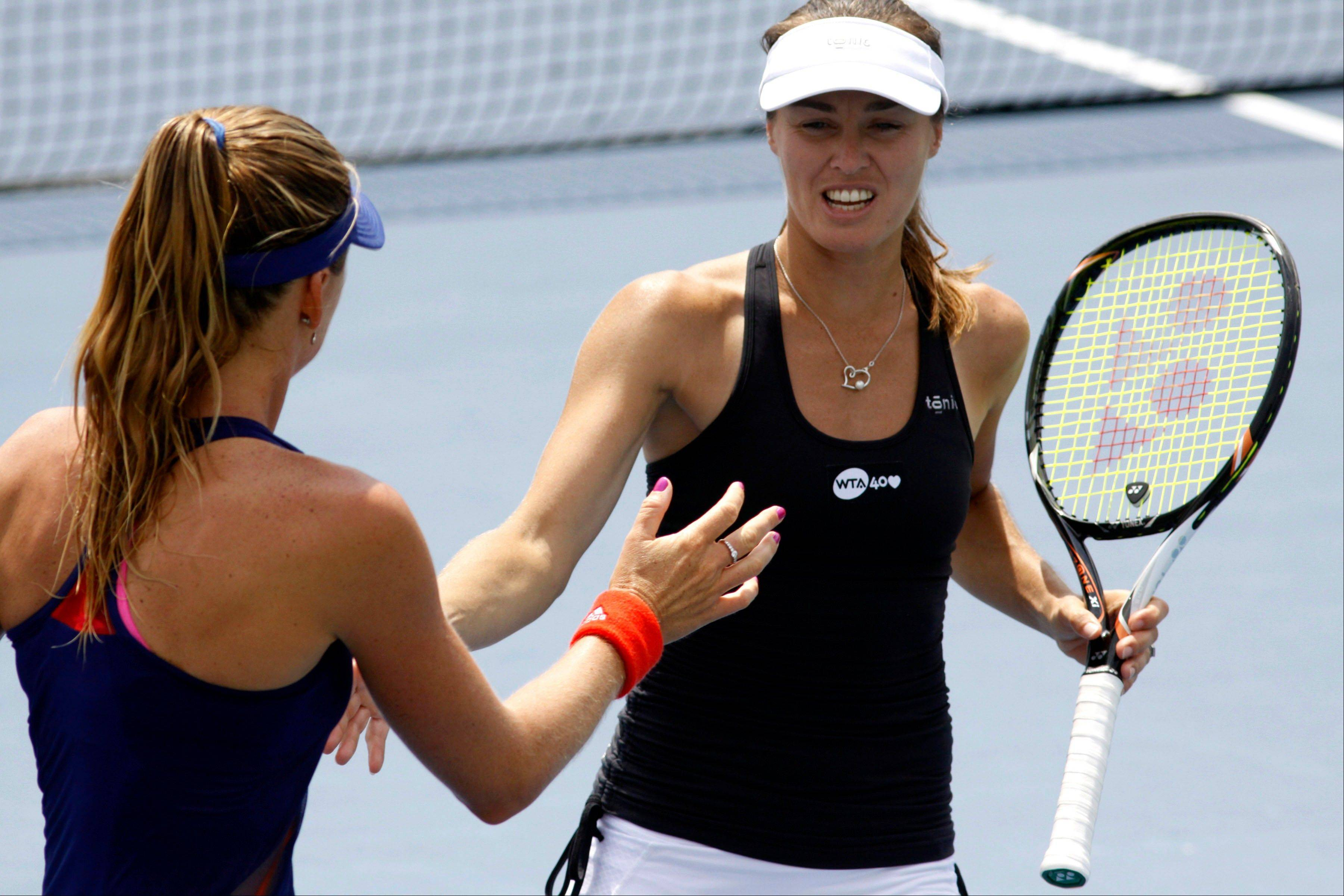 Martina Hingis, of Sweden, right, congratulates teammate Daniela Hantuchova, of Slovakia, after scoring a point against Anabel Medina Garrigues, of Spain, and Flavia Pennetta, of Italy, during a doubles match at the Western & Southern Open tennis tournament on Monday, Aug. 12, 2013, in Mason, Ohio.