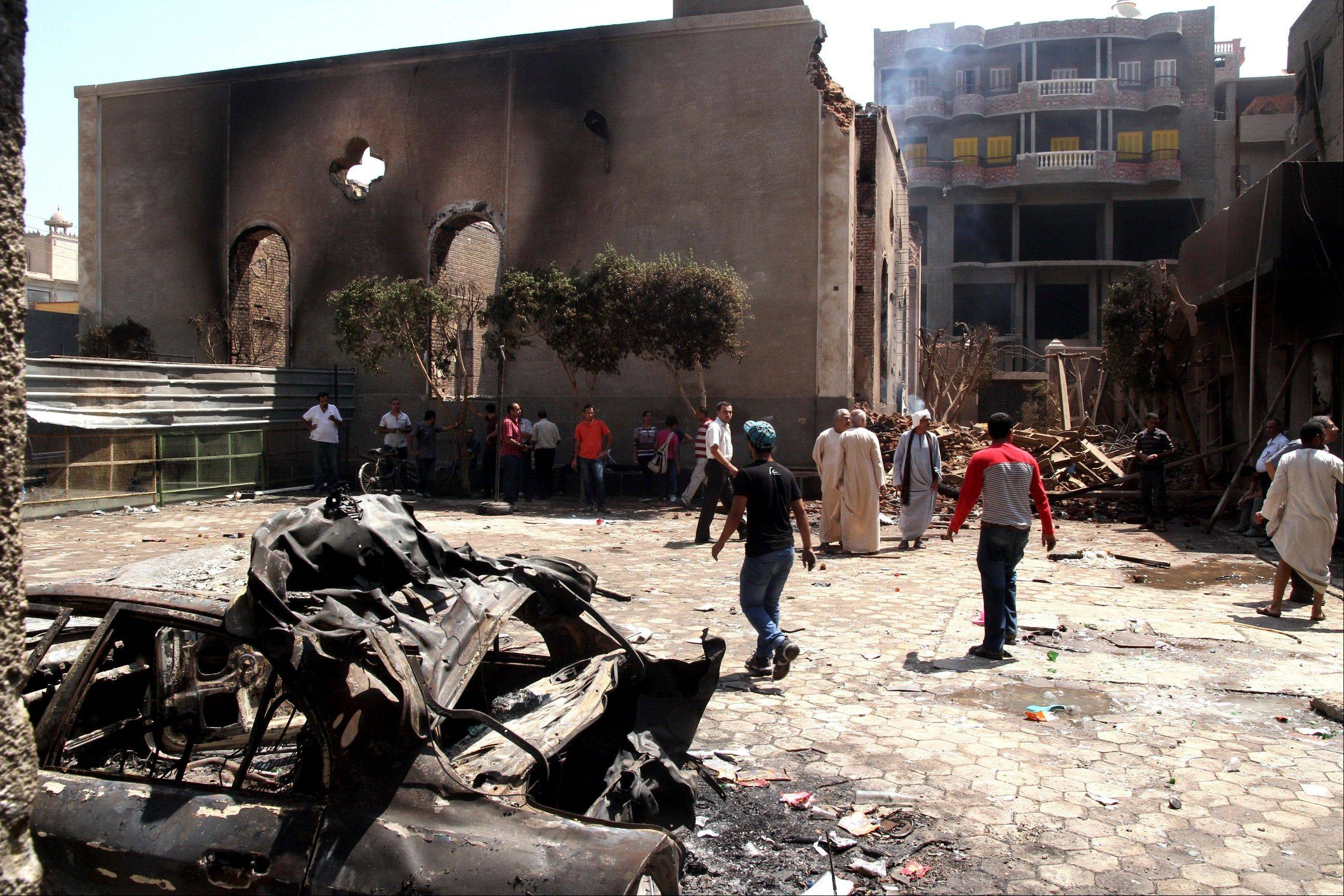 Egyptian gather Saturday in the ruins of the Evangelical Church of Malawi after it was ransacked, looted and burned on Thursday by an angry mob, in Malawi. In the province south of Cairo, protesters attacked two Christian churches, security officials said.