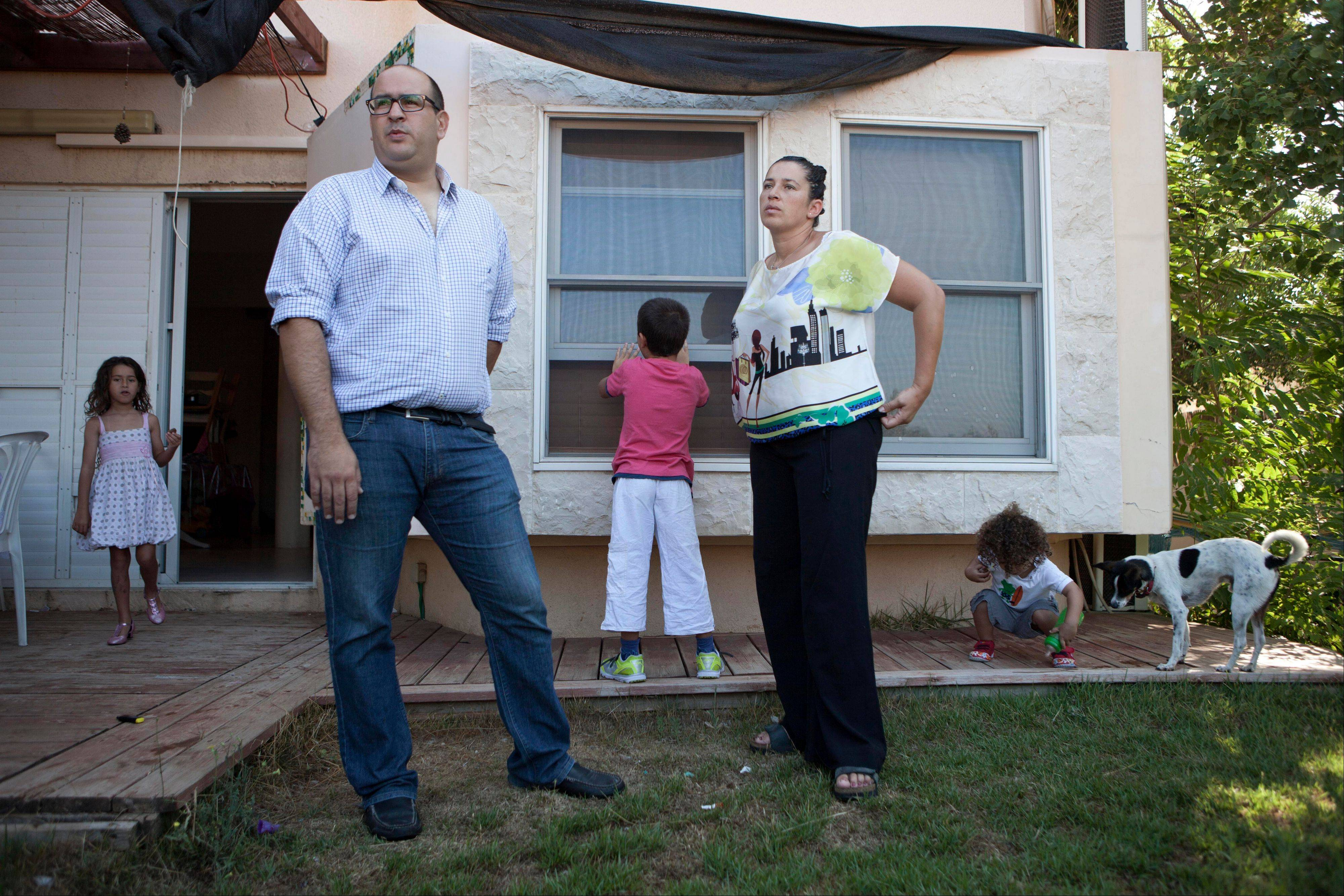 In this Sunday, Aug. 11, photo, Micha Drori, his wife, Ora, and their children stand in the garden of their house at the settlement of Barkan in the West Bank. Israel has built dozens of settlements since 1967 that are now home to about 550,000 Israelis. Settlements dot the West Bank, the heartland of a future Palestine, and ring East Jerusalem, the Palestinians� hoped-for capital, making it ever more difficult to partition the land between two states. Jews now make up 17.5 percent of the population in both areas.