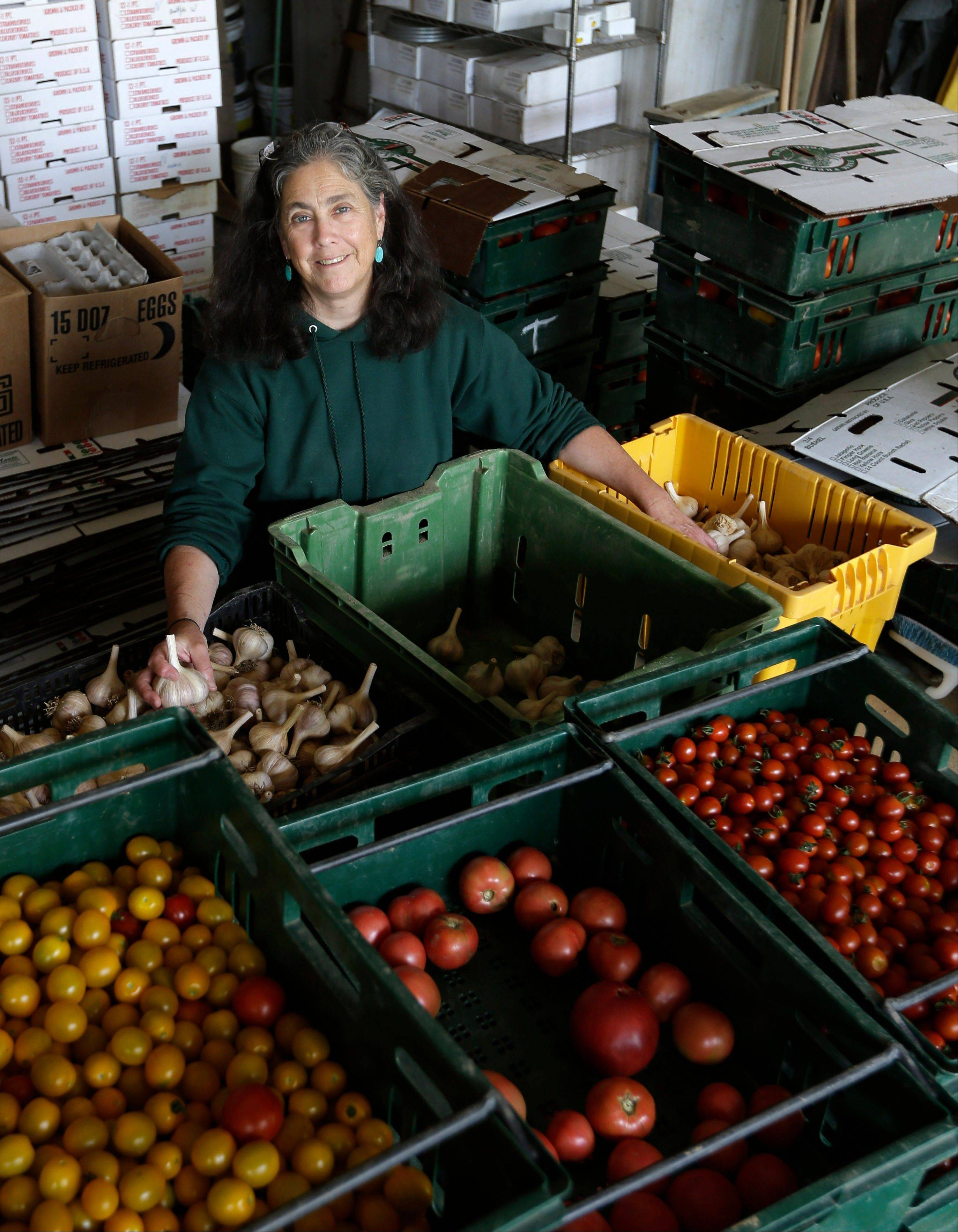Justine Denison poses with fresh produce at Denison Farm on Aug. 12 in Schaghticoke, N.Y. Justine and Brian Denison adhere to all the growing practices required for organic certification, but if they label their beans and tomatoes �organically grown,� they could face federal charges and $20,000 or more in fines. That�s why they and hundreds of other small direct-marketing farms across the country have adopted an alternative label: Certified Naturally Grown. Certified farms pledge to follow organic practices, while avoiding the high fee and extensive paperwork required for the federal organic label.