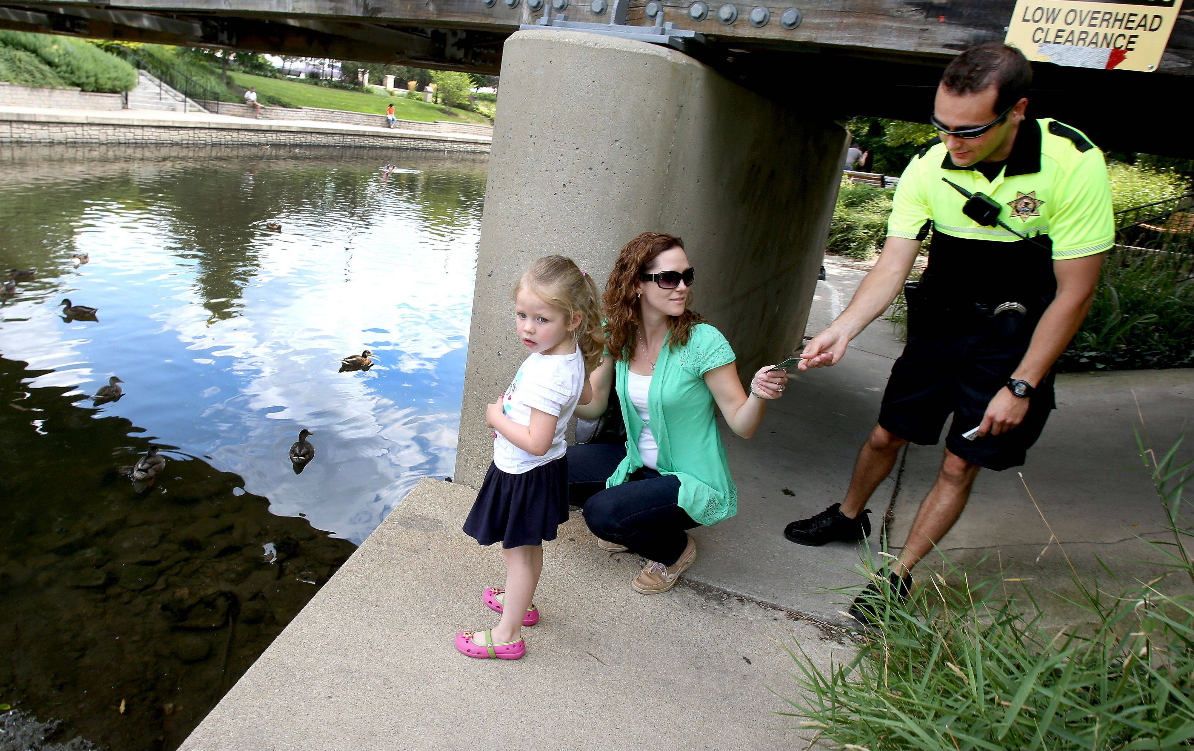 Naperville Park District police officer Patrick Ryan gives Beth Louthain of Naperville a card, shown below, that reminds people not to feed the wildlife. Louthain was watching � but not feeding � the ducks with daughter Kendall, 4, along the Riverwalk.