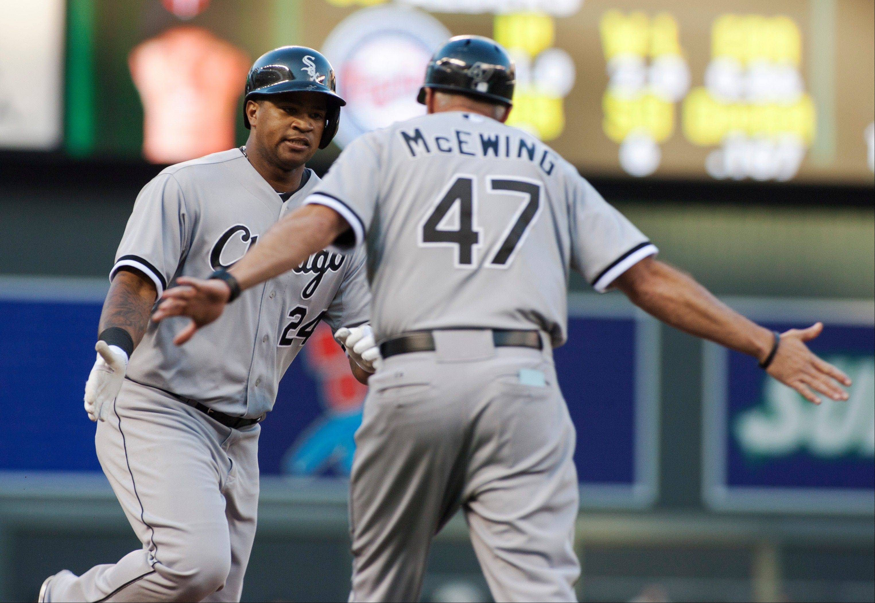 Chicago White Sox�s Dayan Viciedo, left, is congratulated by third base coach Joe McEwing (47) after hitting a three-run home run during the fourth inning of an baseball game Saturday against the Minnesota Twins in Minneapolis.
