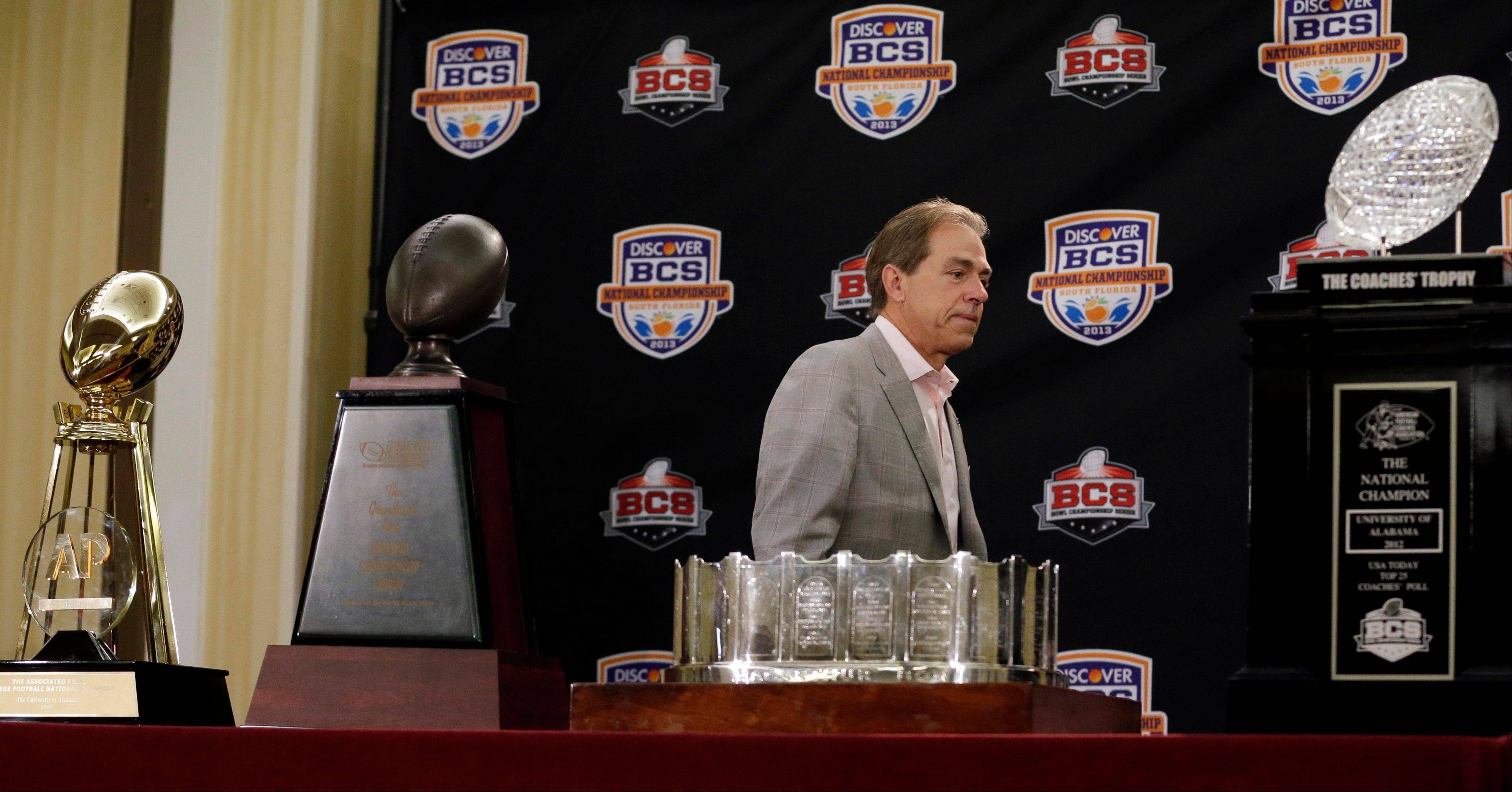 In this Jan. 8, 2013, file photo, Alabama head coach Nick Saban walks past national championship trophies at a BCS National Championship college football news conference in Ft. Lauderdale, Fla. Alabama will begin this season the way it ended the last two � No. 1. Nick Saban and the two-time defending national champion Crimson Tide are top-ranked in The Associated Press preseason college football poll released Saturday as they try to become the first team to win three straight national titles.