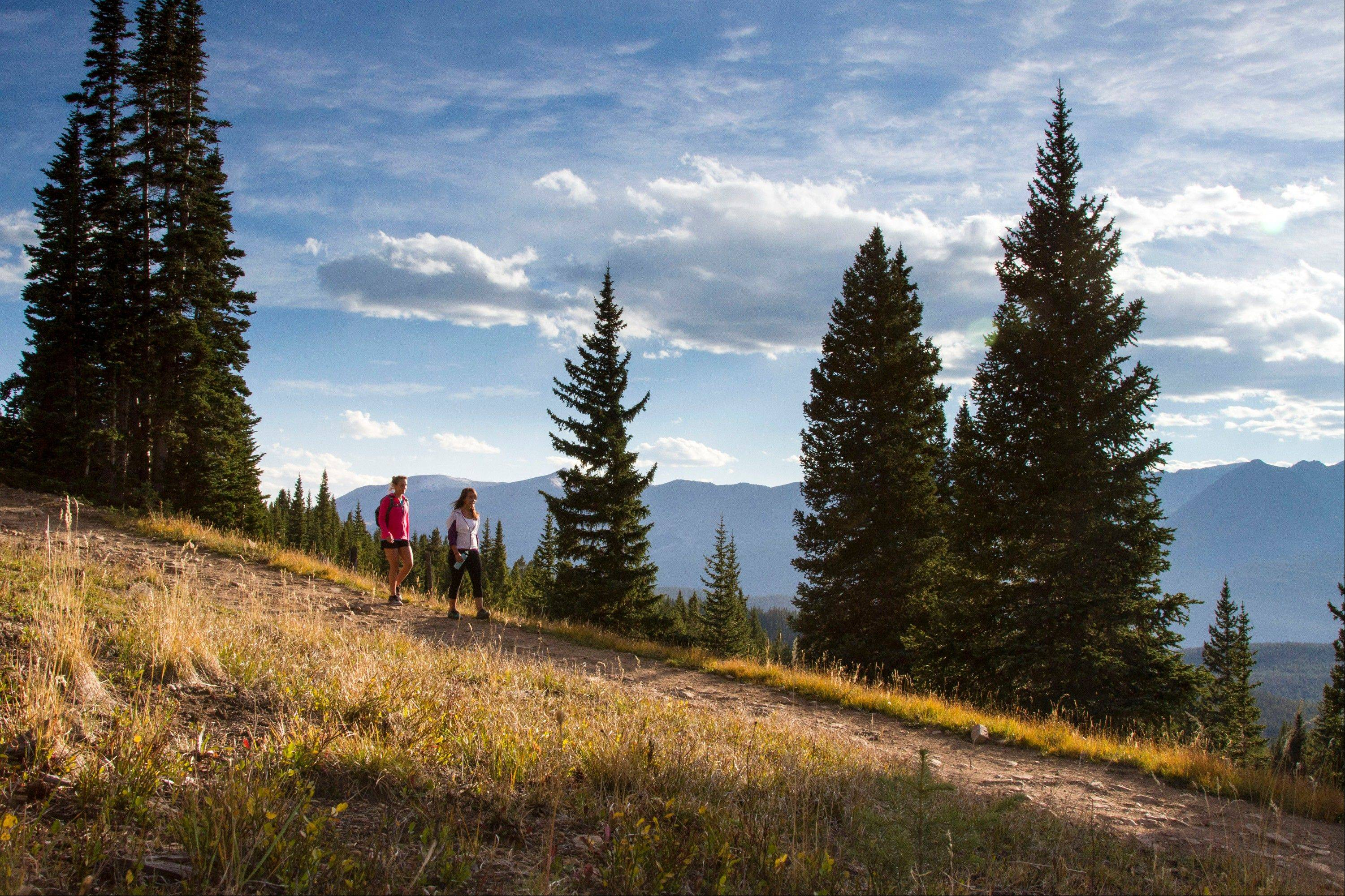 Hikers on a hilly trail in Breckenridge, Colo. Breckenridge may be best known as a ski resort, but it offers many summer and fall activities for visitors, along with offseason deals.