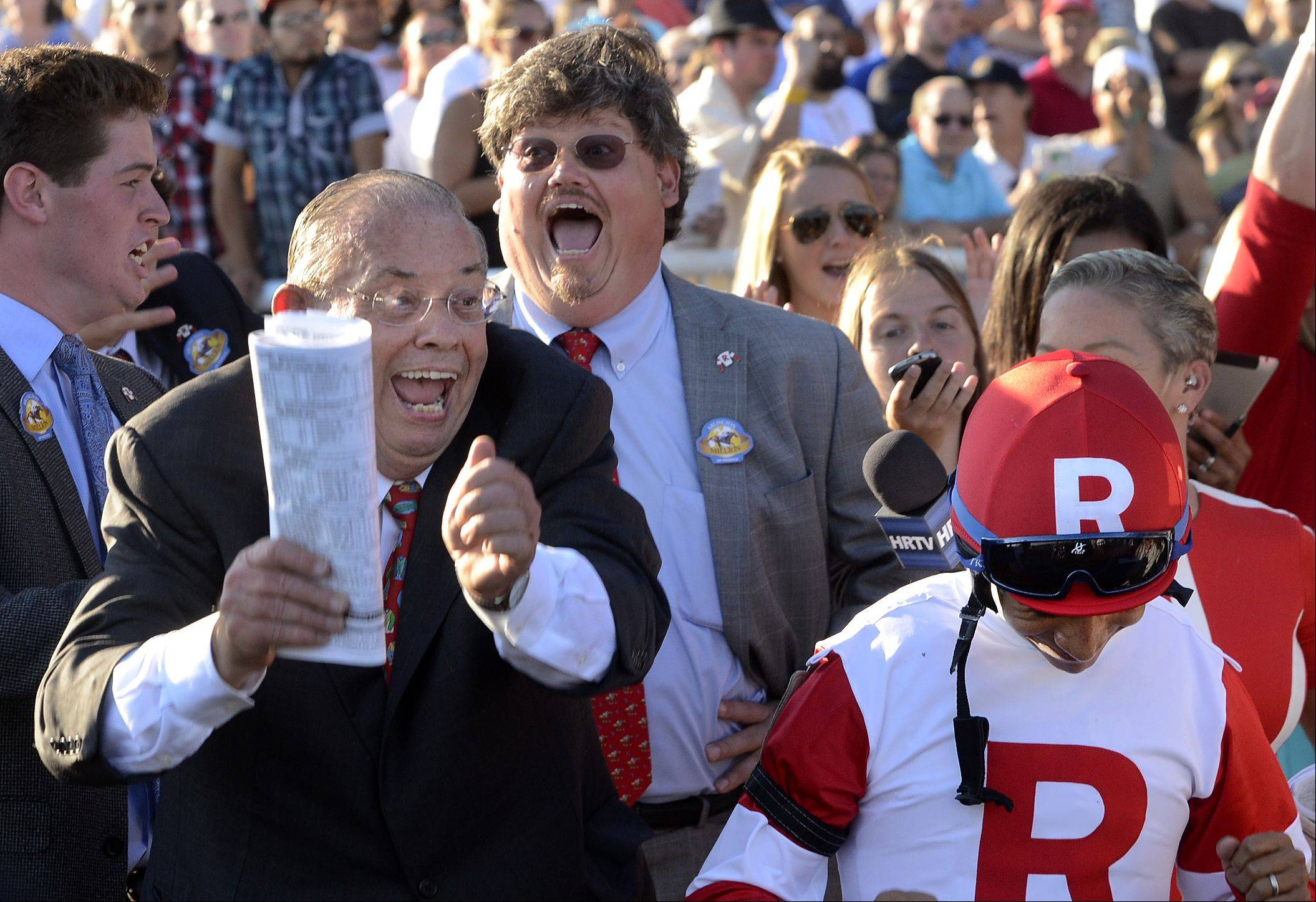 Real Solution owner Kenneth L. Ramsey celebrates with jockey Alan Garcia after being announced the winner of the Arlington Million during the Arlington International Festival of Racing at Arlington International Racecourse.