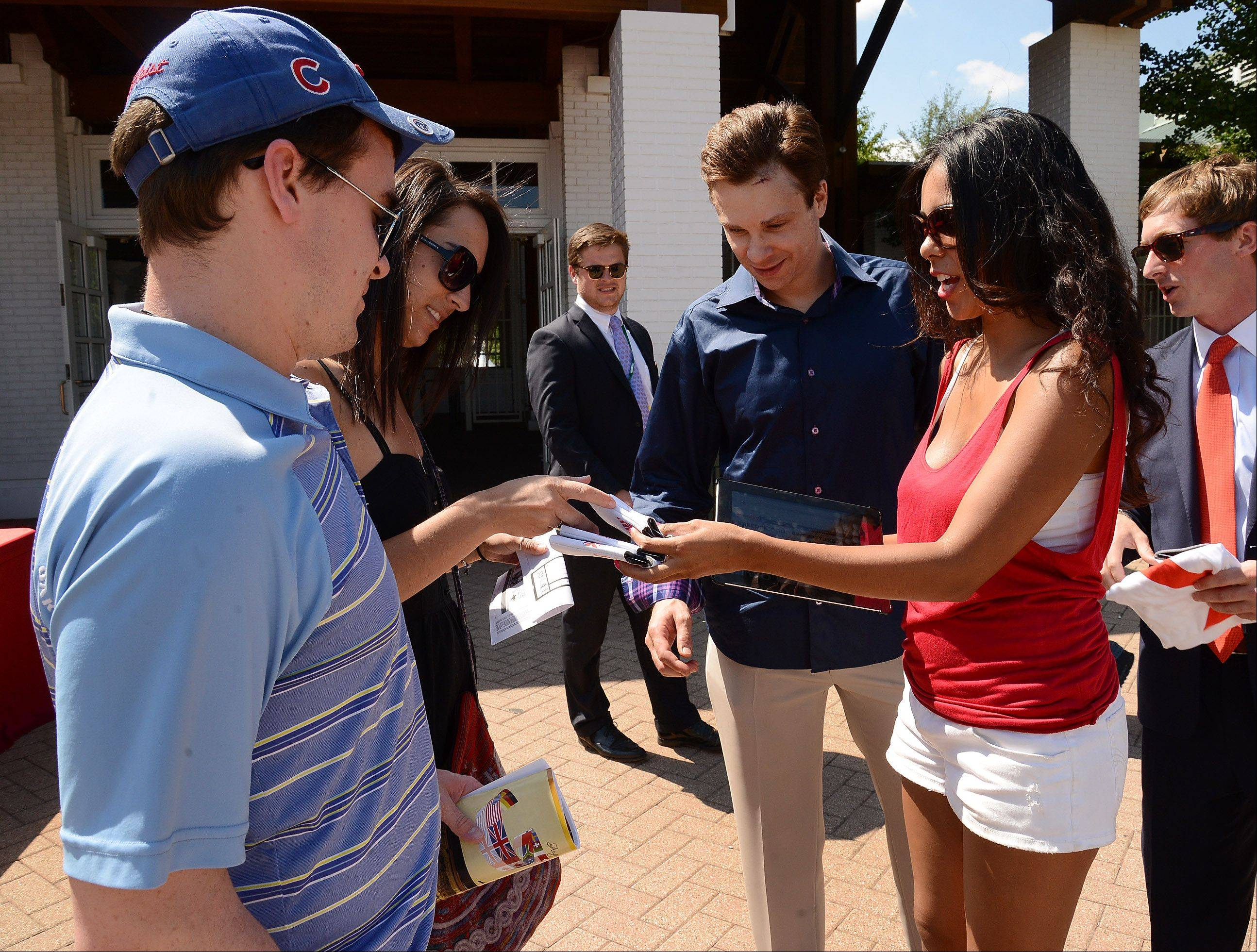 America's Best Racing Ambassador Vanessa Ceron of Elgin, hands out gifts to from left, Mark Lennon, Jill Hackmaster and Scott Youngren, all of Chicago, at the Arlington International Festival of Racing at Arlington International Racecourse.