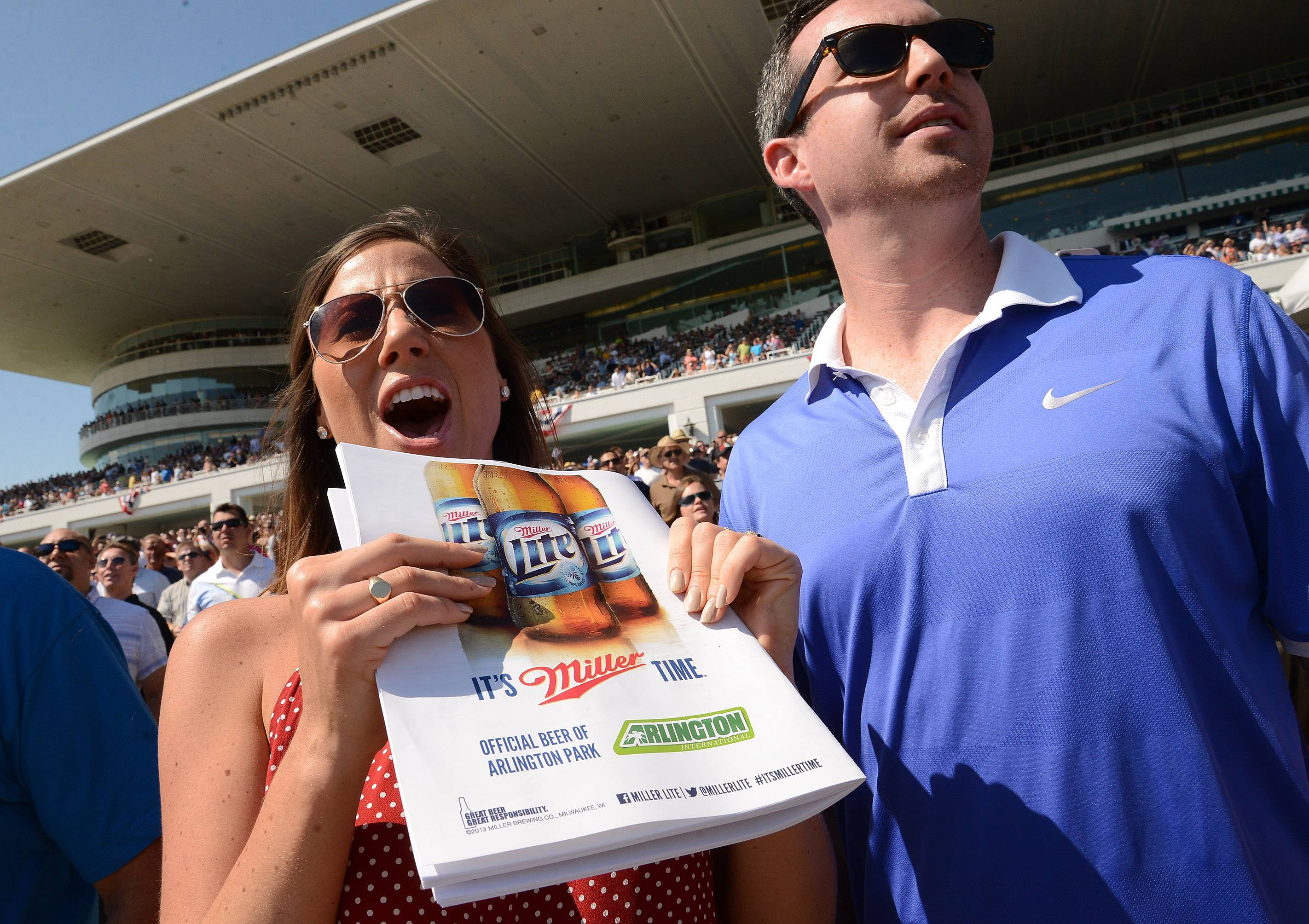 Bridget Comeau and Dan O'Connell, both of Chicago, cheer on their horse during the Arlington International Festival of Racing at Arlington International Racecourse.