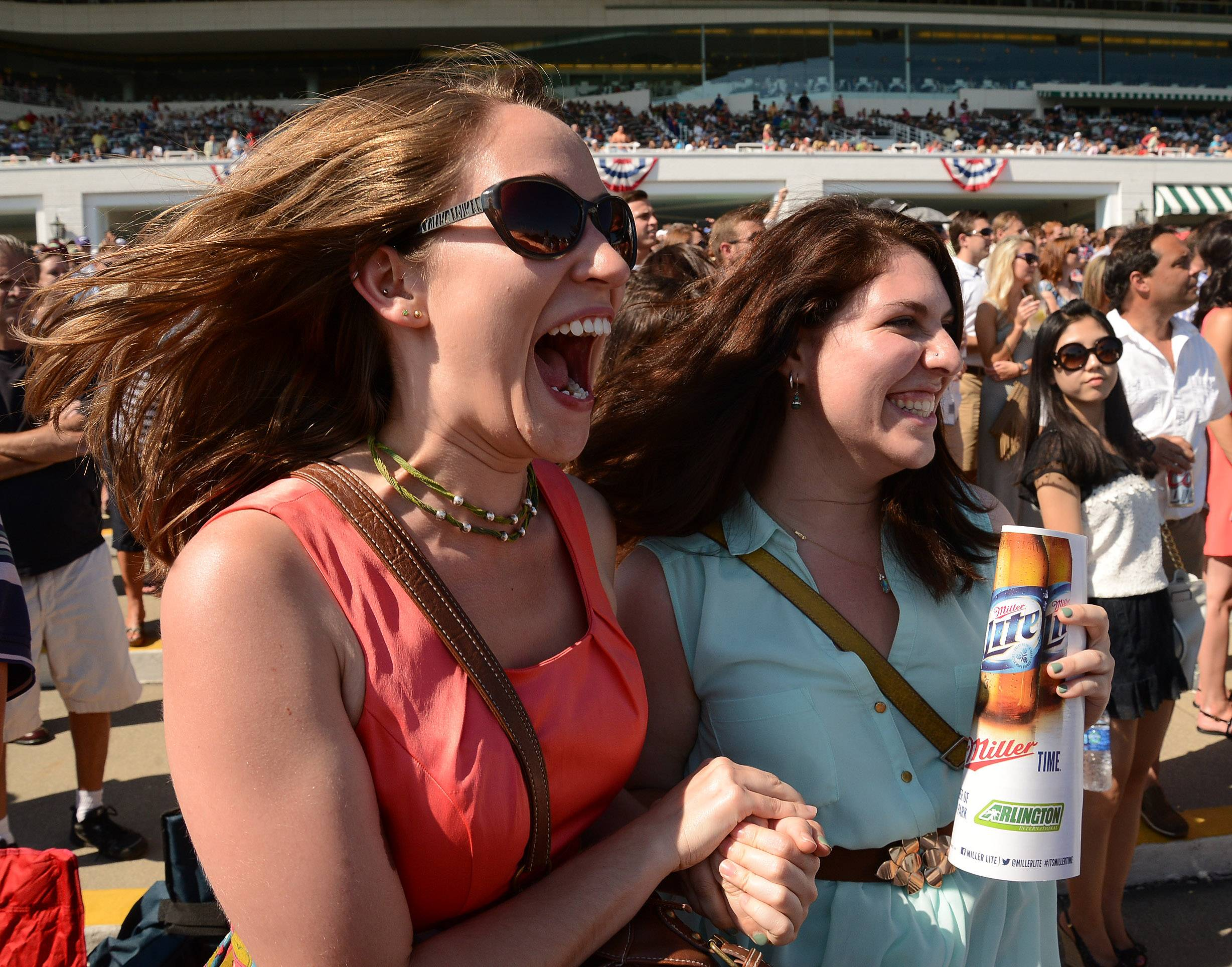Elisa Hilderbrand and Nina Litoff, both of Chicago, cheer on their horse during the Arlington International Festival of Racing at Arlington International Racecourse.