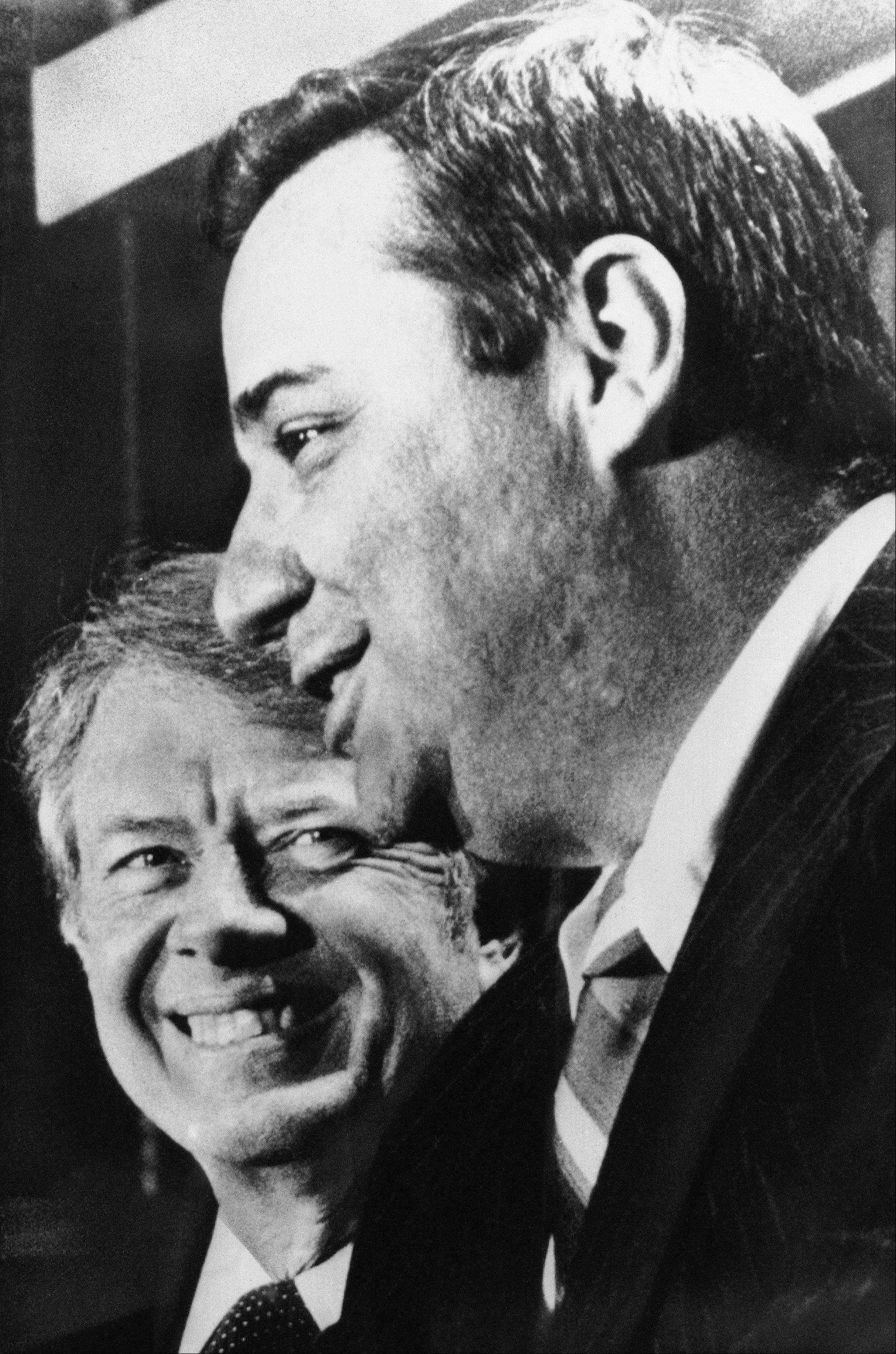 President Jimmy Carter smiles as he listens to Bert Lance, foreground, his choice for Director of the Office of Management and the Budget.