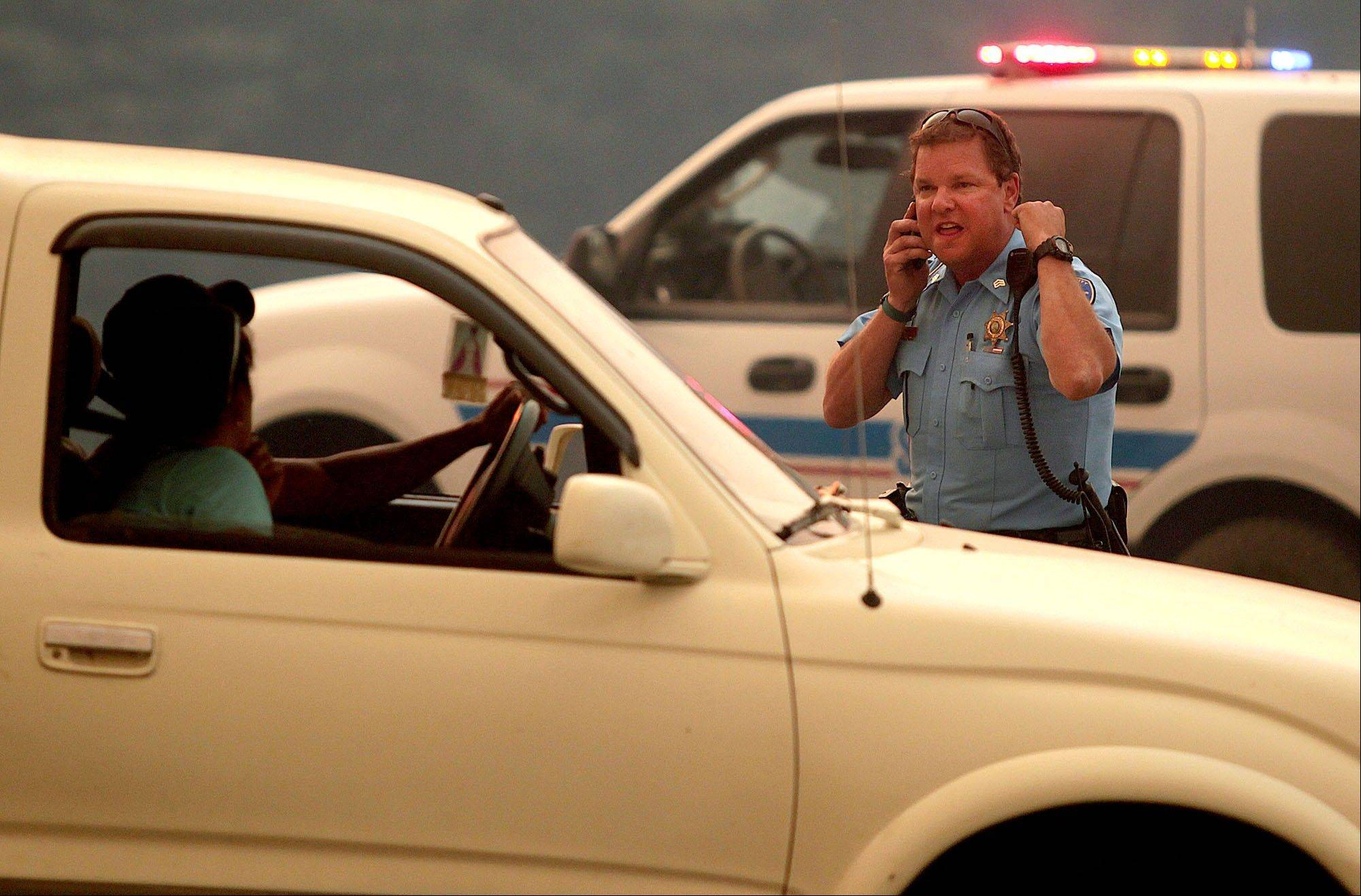 A member of the Blaine County Sheriff Department enforces the closure of Idaho Highway 75.