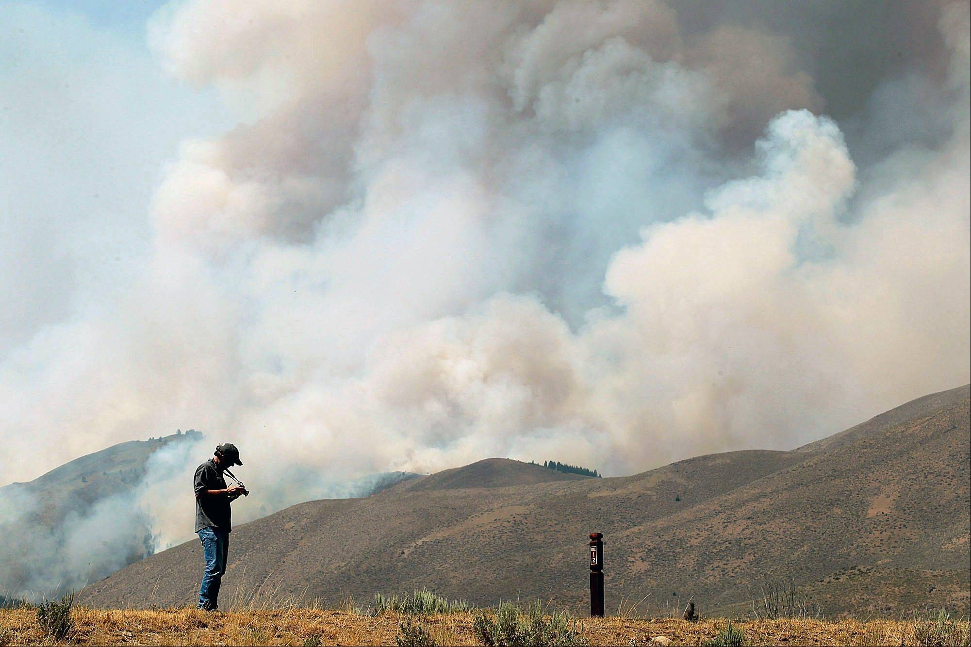 A man photographs the 44,000 acre Beaver Creek Fire on Thursday, northwest of Hailey, Idaho.