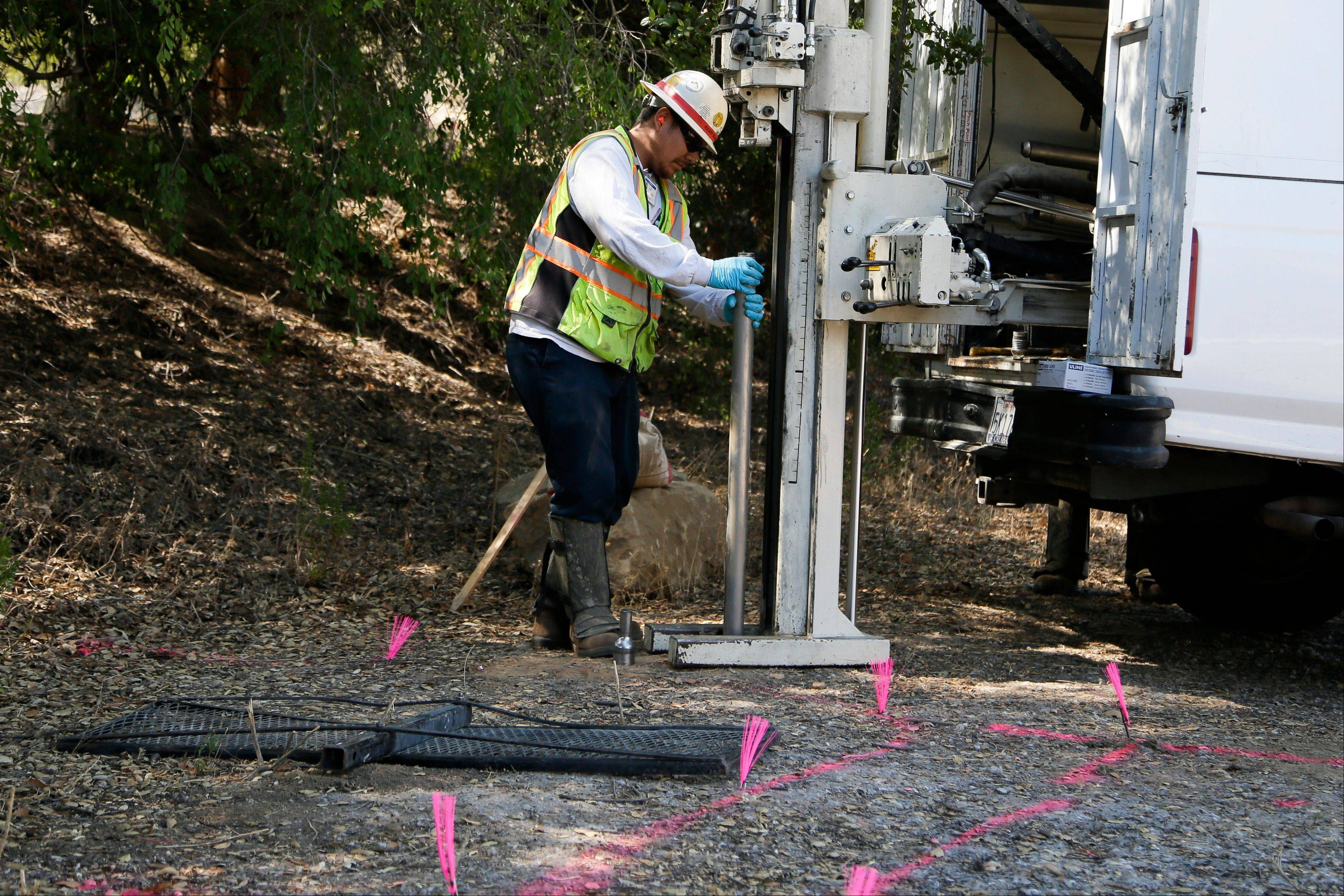 A worker drives a metal rod into the ground to collect soil samples at the Santa Susana Field Laboratory.