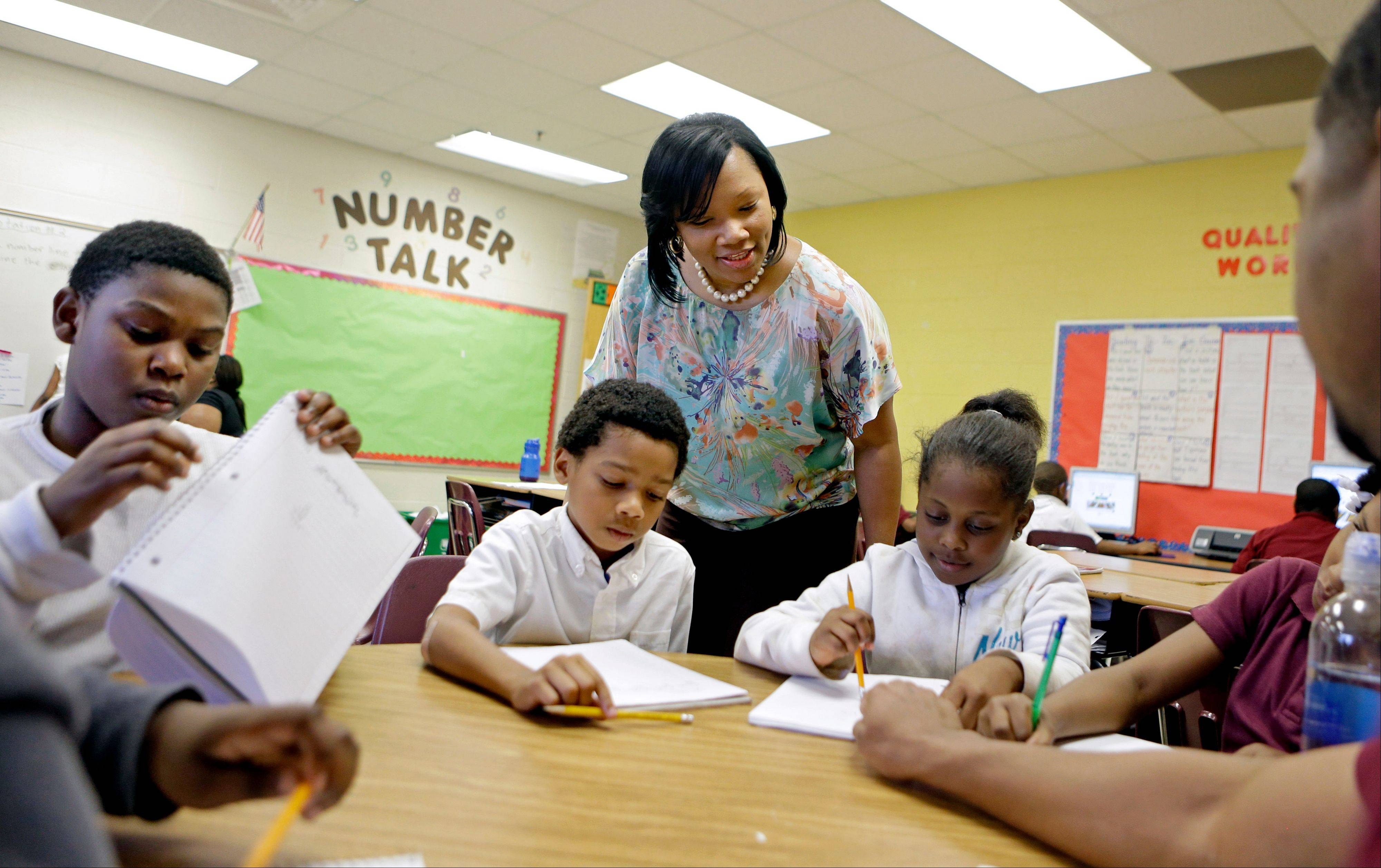Associated PressBurgess-Peterson Elementary School principal Robin Robbins, center, meets with students during an after-school study program in Atlanta, in preparation for state standardized testing, soon to begin. A new poll from The Associated Press-NORC Center for Public Affairs Research finds parents of school-age children view standardized tests as a useful way to track student progress and school quality.