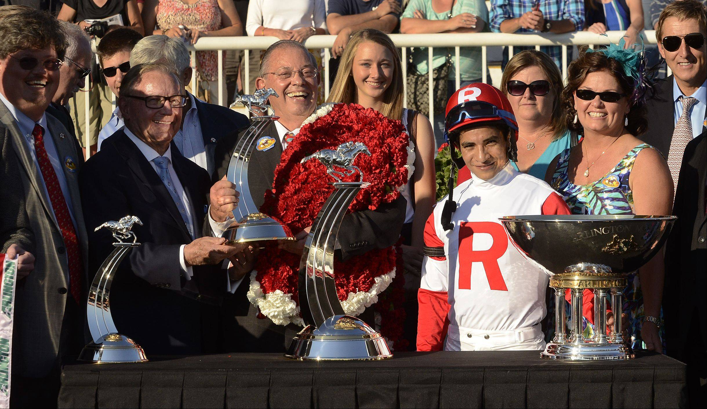 Richard L. Duchossois presents the trophy to Real Solution owner Kenneth L. Ramsey and jockey Alan Garcia on Saturday after the 31st running of the Arlington Million.