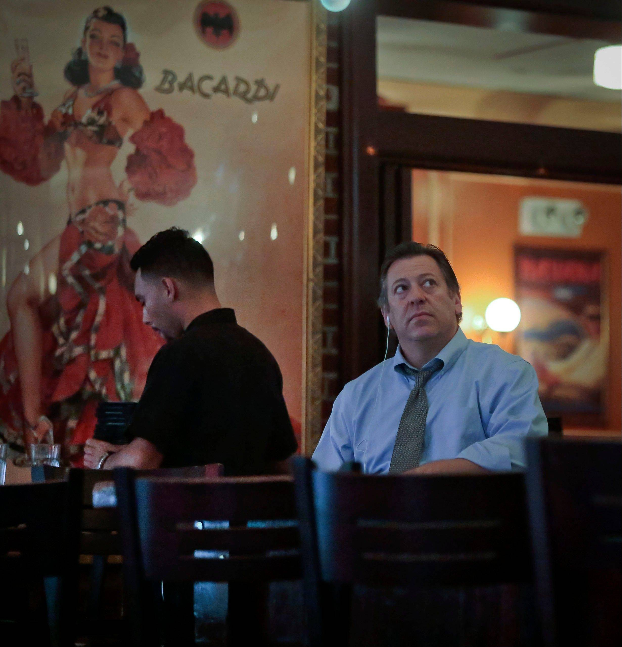 In this Thursday, Aug. 8, 2013, photo, Jeremy Merrin, right, owner of Havana Central restaurants, reacts to a television nearby as a worker prepares for customes to arrive in New York. Merrin said that while he supports healthcare reform, the current changes under President Obama will hurt small businesses like his.