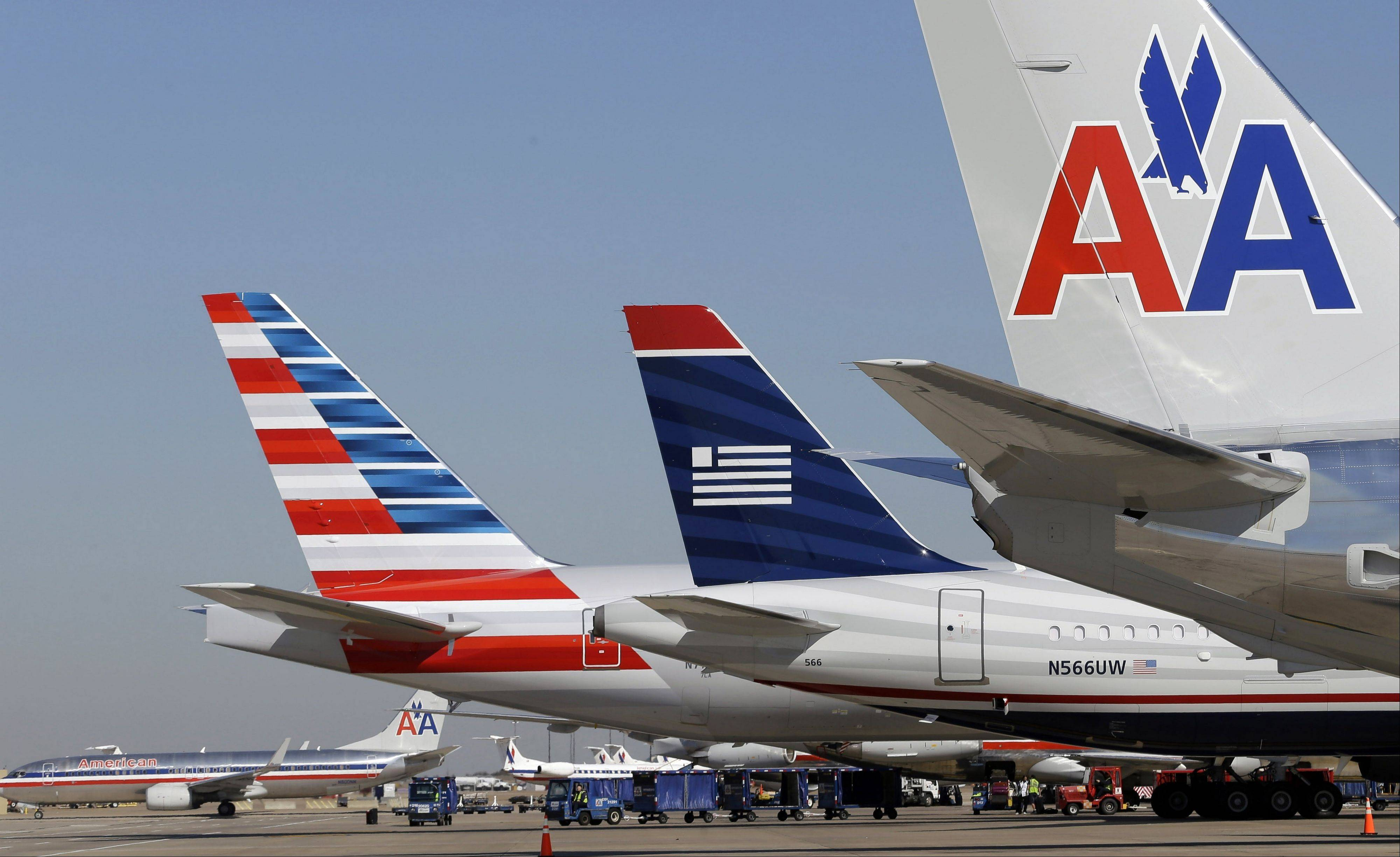 US Airways and American Airlines planes are shown at gates at DFW International Airport in Grapevine, Texas. The Justice Department and a number of state attorneys general on Tuesday, Aug. 13, 2013, challenged a proposed $11 billion merger between US Airways Group Inc. and American Airlines' parent company, AMR Corp.
