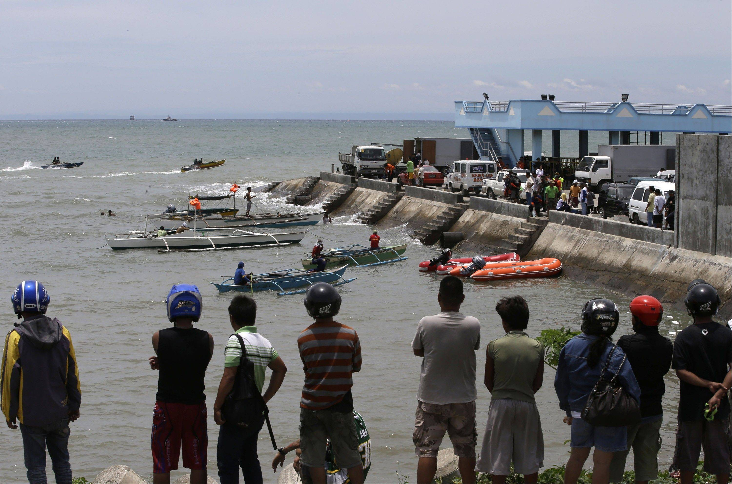 A crowd watches as divers continue their search and rescue operation off Talisay coast, Cebu province Sunday, Aug. 18, 2013 following Friday night's collision of the passenger ferry MV Thomas Aquinas and the cargo ship MV Sulpicio Express Siete in central Philippines.