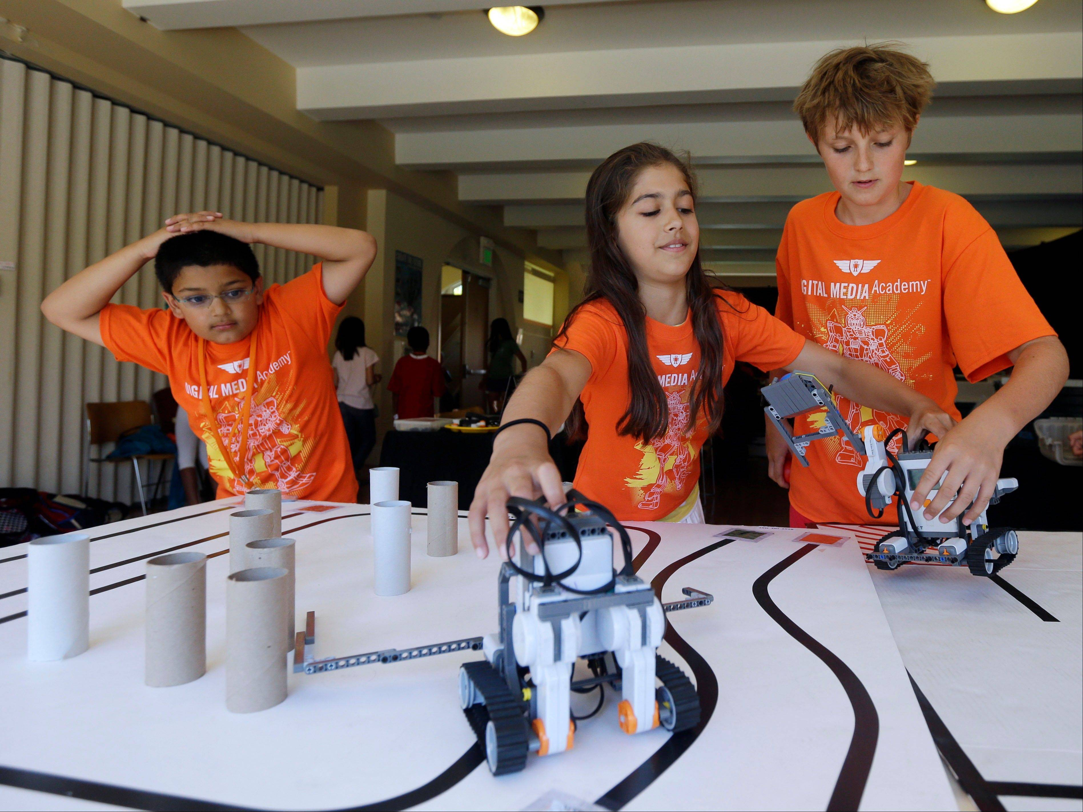 Saci Marty, 10, center, and Callum Brown, 11, at right, put their robotic Lego Mindstorms units through an obstacle course during a Digital Media Academy workshop, in Stanford, Calif.