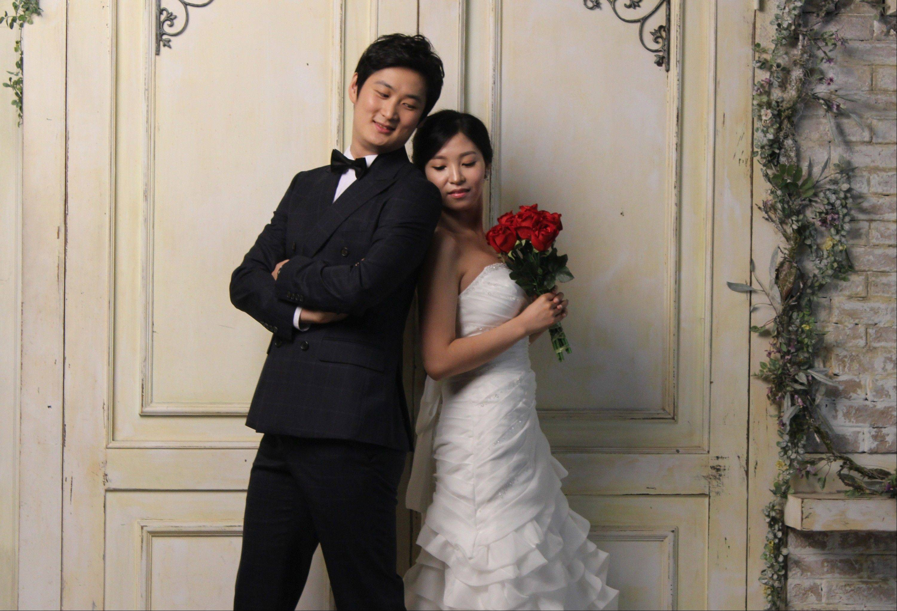 In this Tuesday, July 30, 2013 photo, Chen Jingjing, left, and Yang Candi of Beijing, China, strike a pose at a wedding studio in southern Seoul, South Korea, during an eight-hour photo session part of a South Korean wedding tourism package for Chinese couples. China is the source of one quarter of all tourists to South Korea, and a handful of companies in South Koreans $15 billion wedding industry are wooing an image-conscious slice of the Chinese jet set happy to drop several thousand dollars on a wedding album with a South Korean touch.
