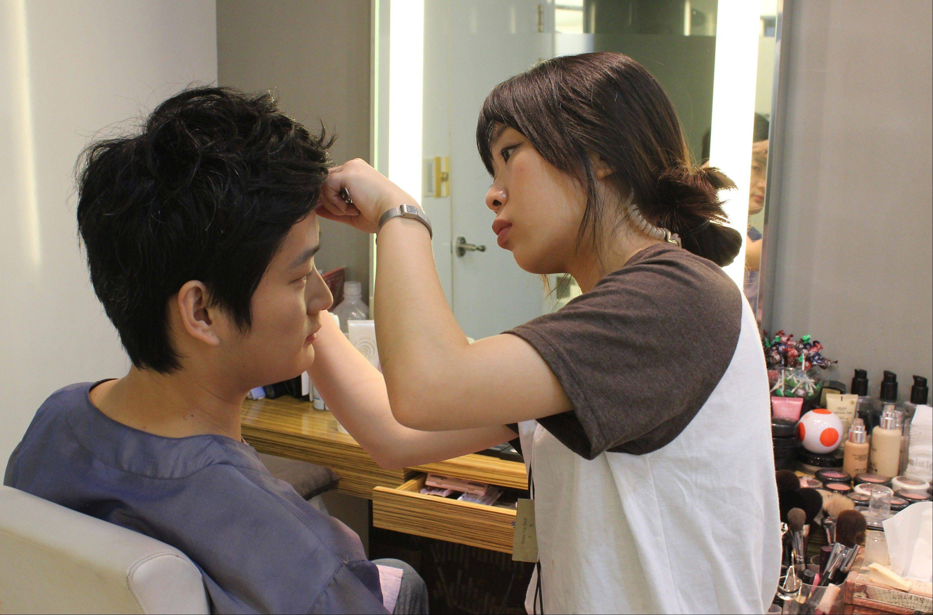 In this July 30, 2013 photo, Chen Jingjing of Beijing, China, tilts his head as a South Korean stylist fills in Chen�s eyebrows with a pencil in southern Seoul, South Korea. China is the source of one quarter of all tourists to South Korea, and a handful of companies in South Koreans $15 billion wedding industry are wooing an image-conscious slice of the Chinese jet set happy to drop several thousand dollars on a wedding album with a South Korean touch.