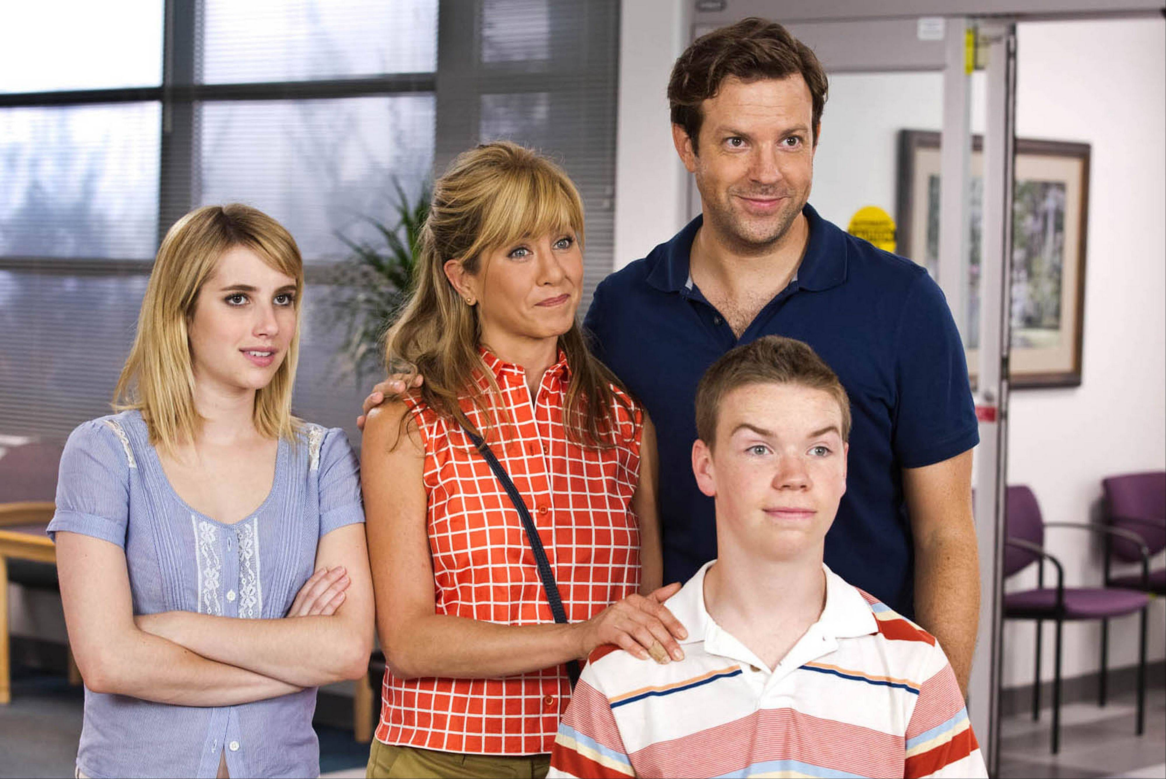 "This film image released by Warner Bros. Entertainment shows, from left, Emma Roberts, Jennifer Aniston, Jason Sudeikis, background right, and Will Poulter in a scene from ""We're the Millers."" The raunchy comedy hung onto second at the box office with a $17 million haul."