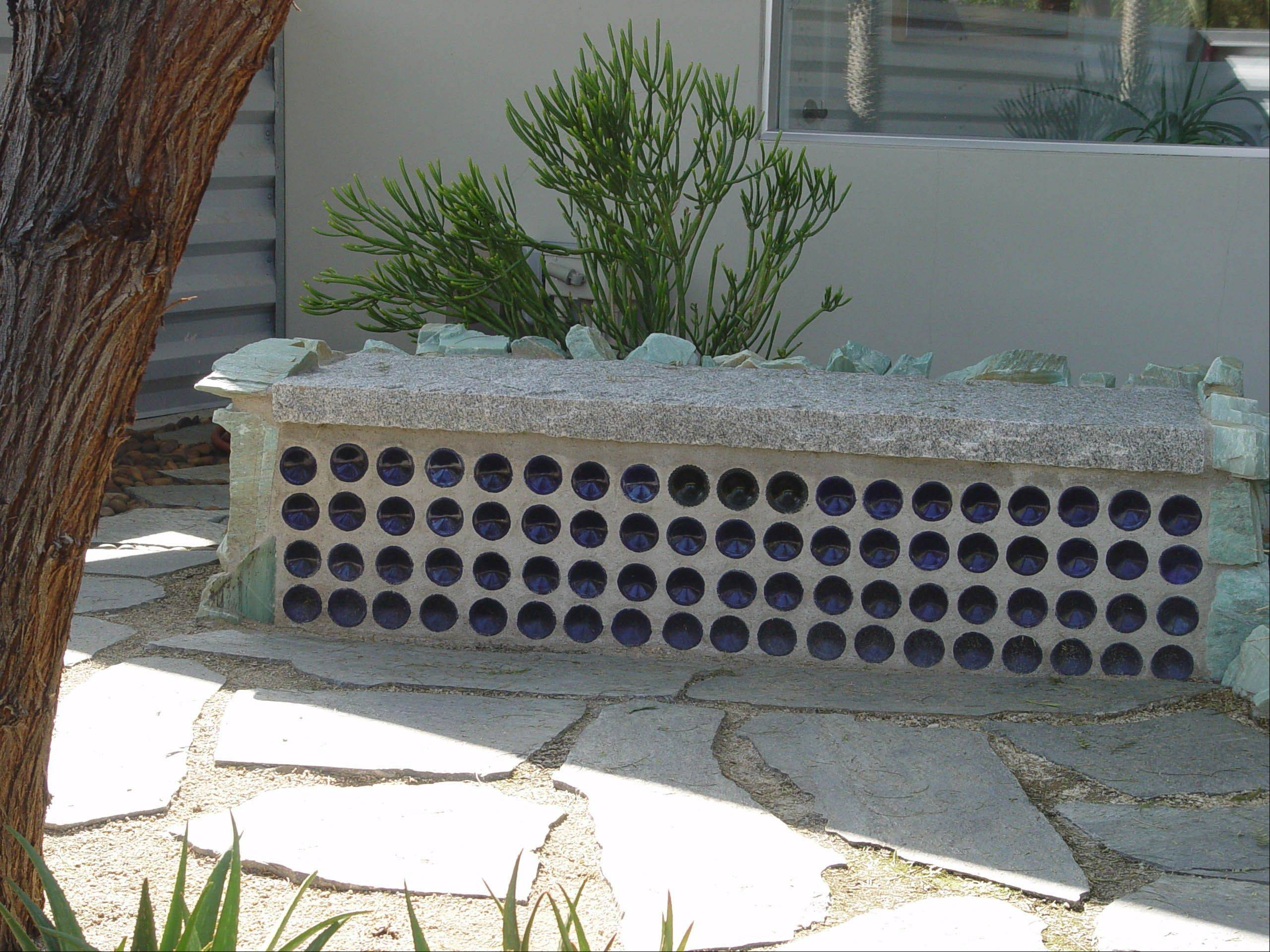 This contemporary bench was built out of identical blue bottles and topped with a clean granite slab.