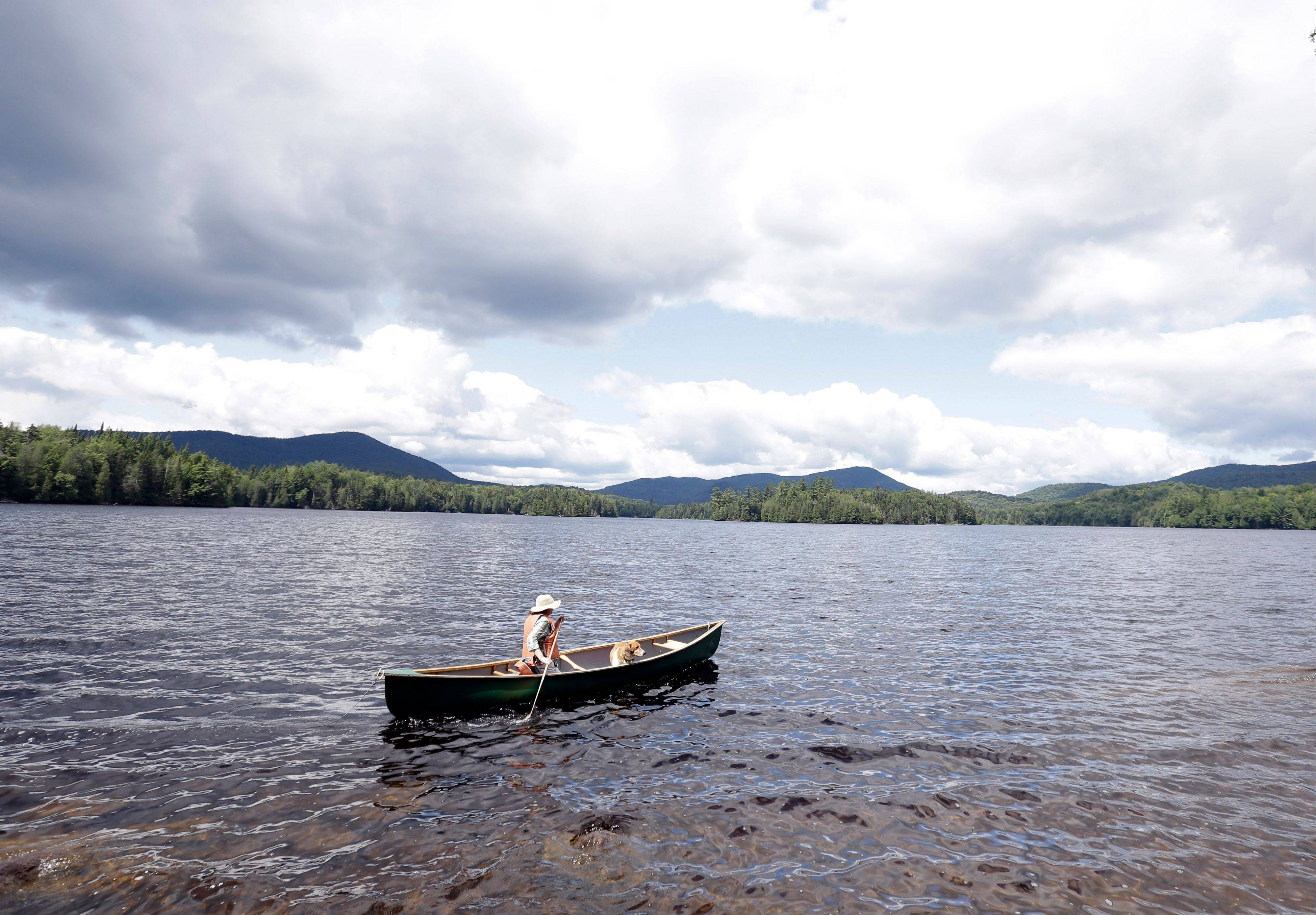 Cynthia Taylor, of Watertown, Mass., canoes along the shoreline of Camp Santanoni on Newcomb Lake with her dog Arlo, in Newcomb, N.Y. Camp Santanoni is an Adirondack Mountain great camp that is being restored.