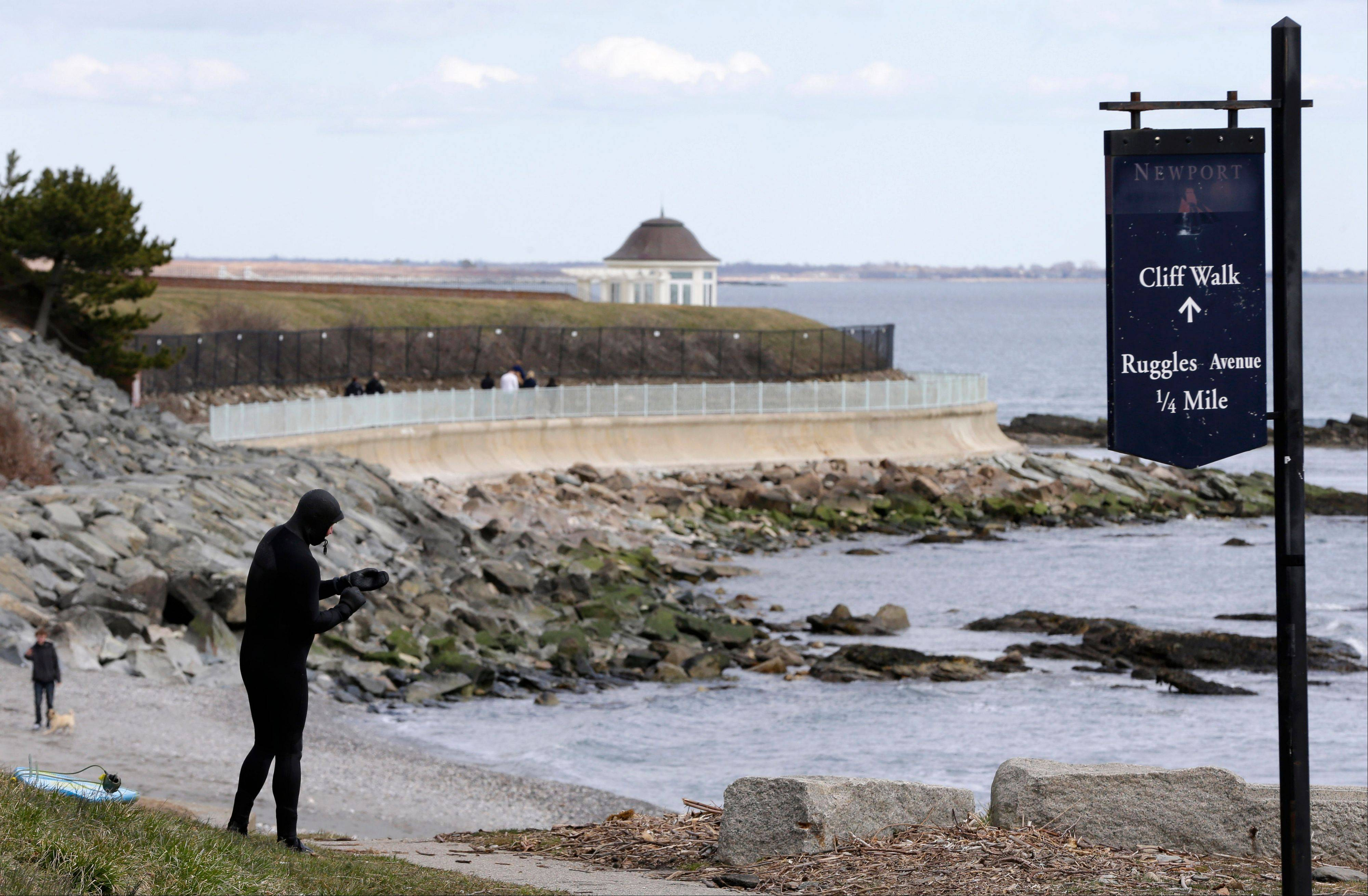 Surfer Dave Livingston, of Newport, R.I., left, removes his gloves while standing near a portion of the Cliff Walk, in Newport, R.I.