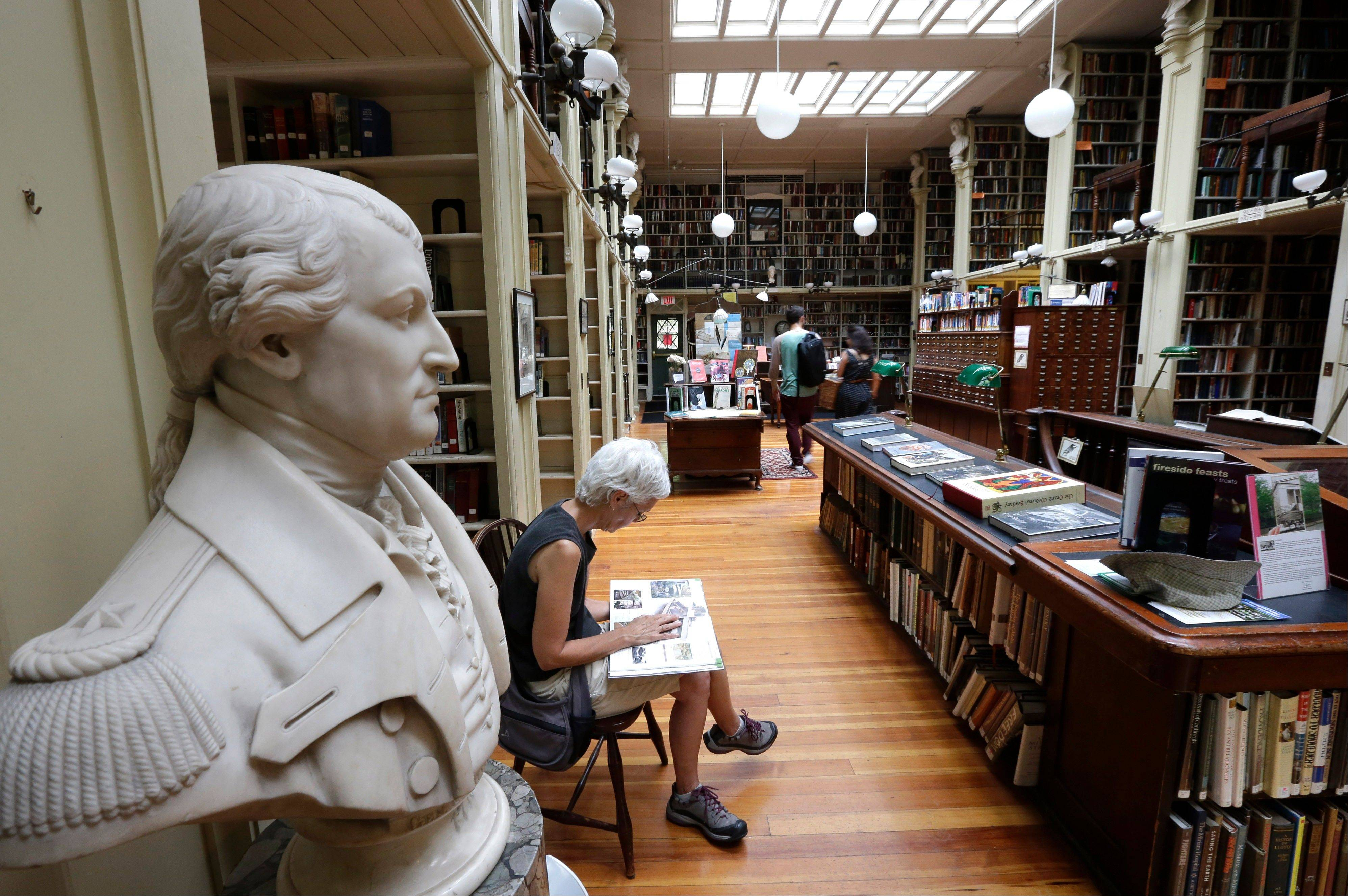 A woman reads while seated next a statue of American Revolutionary War Gen. Nathanael Greene, left, at the Providence Athenaeum, in Providence, R.I.