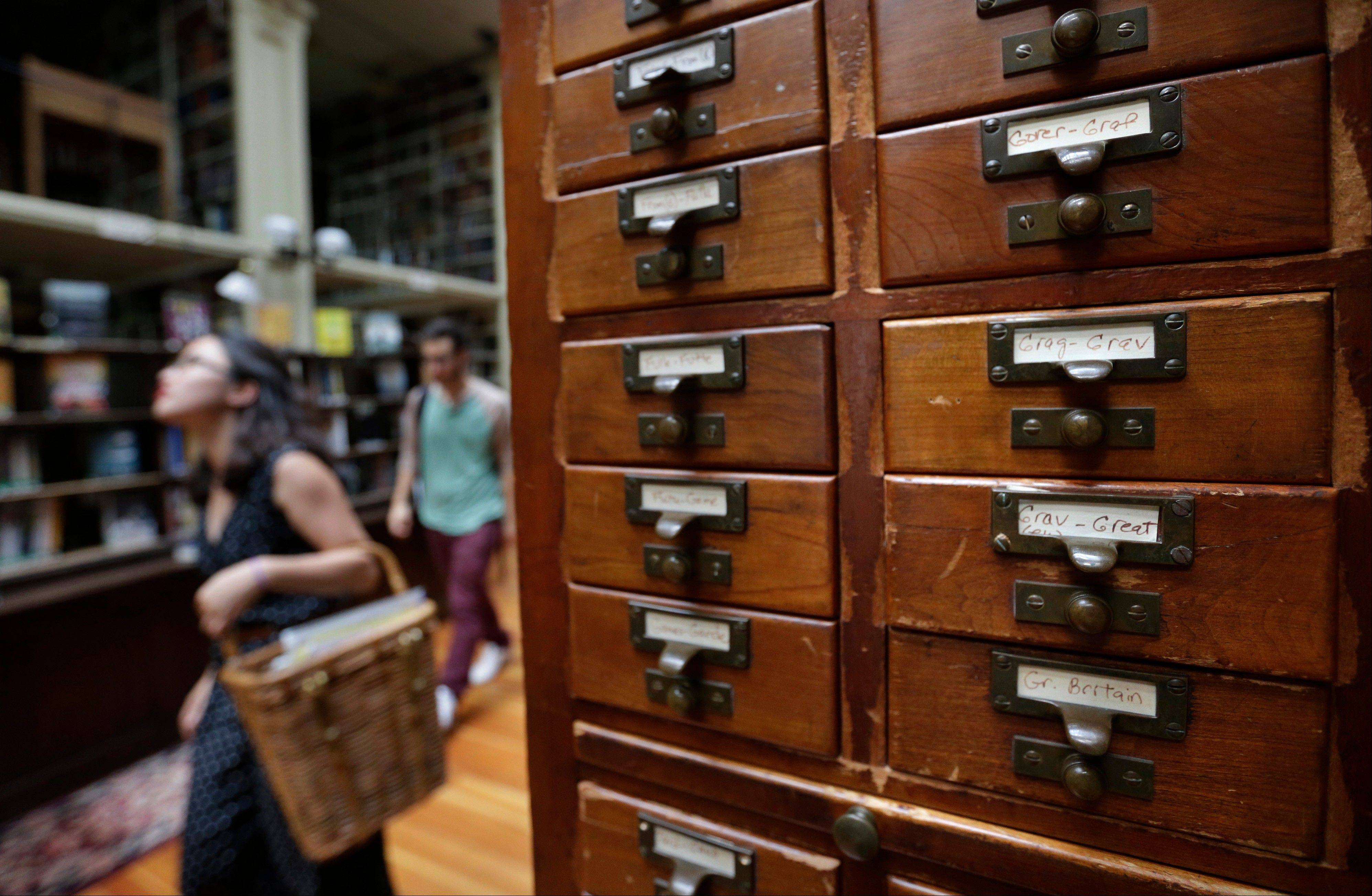 Brown University students Nicha Ratana-Apiromyakij, left, and Nick Melachrinos, walk past a card catalog at the Providence Athenaeum, in Providence, R.I. With roots dating back to 1753, the private library is one of the oldest in the country.