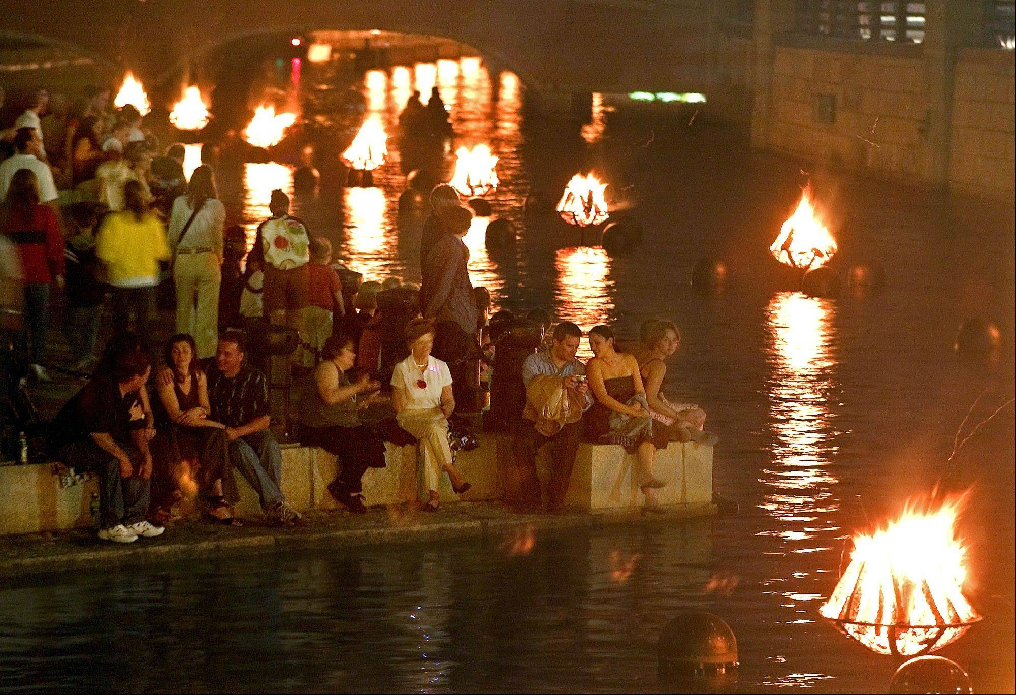 Crowds gather along the riverfront to watch the WaterFire art installation in Providence, R.I. The work by Barnaby Evans centers on a series of 100 bonfires that blaze just above the surface of the three rivers that pass through the middle of downtown.