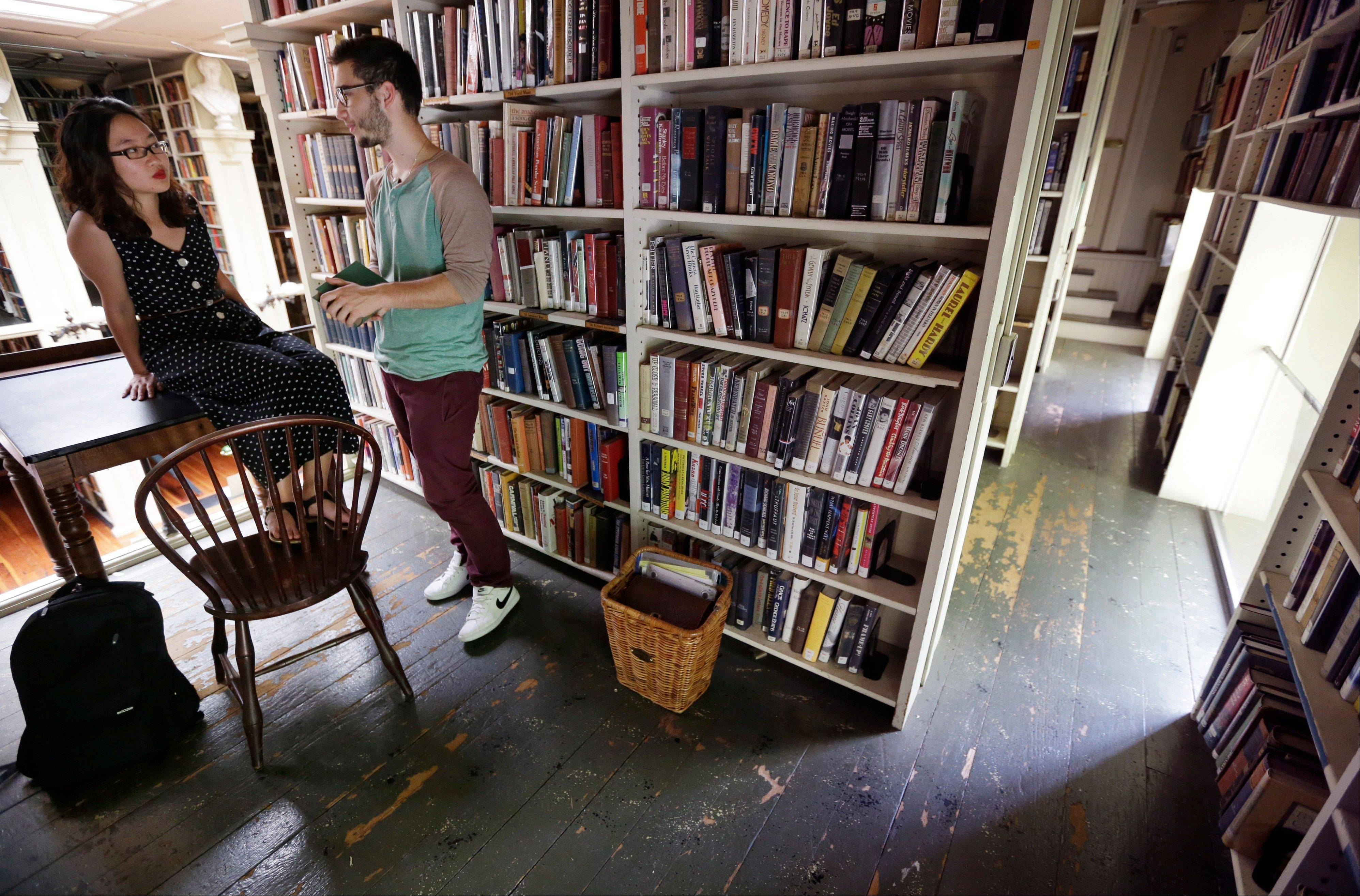 Brown University students Nicha Ratana-Apiromyakij, left, and Nick Melachrinos, stop to talk while visiting the stacks at the Providence Athenaeum, in Providence, R.I.