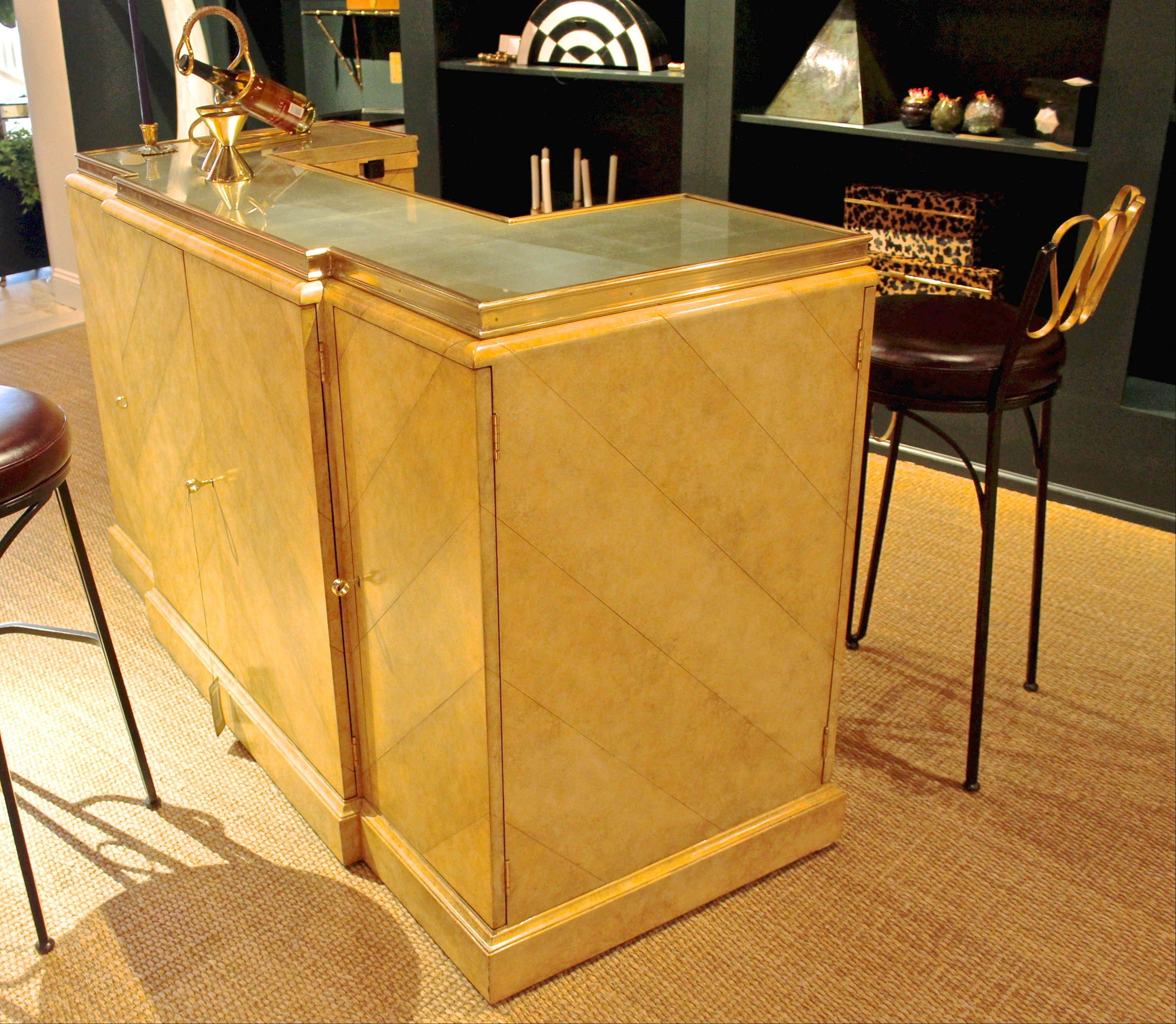 A parchment lacquered leather inlaid bar with silver eglomise top was designed by Celerie Kemble for Maitland-Smith.