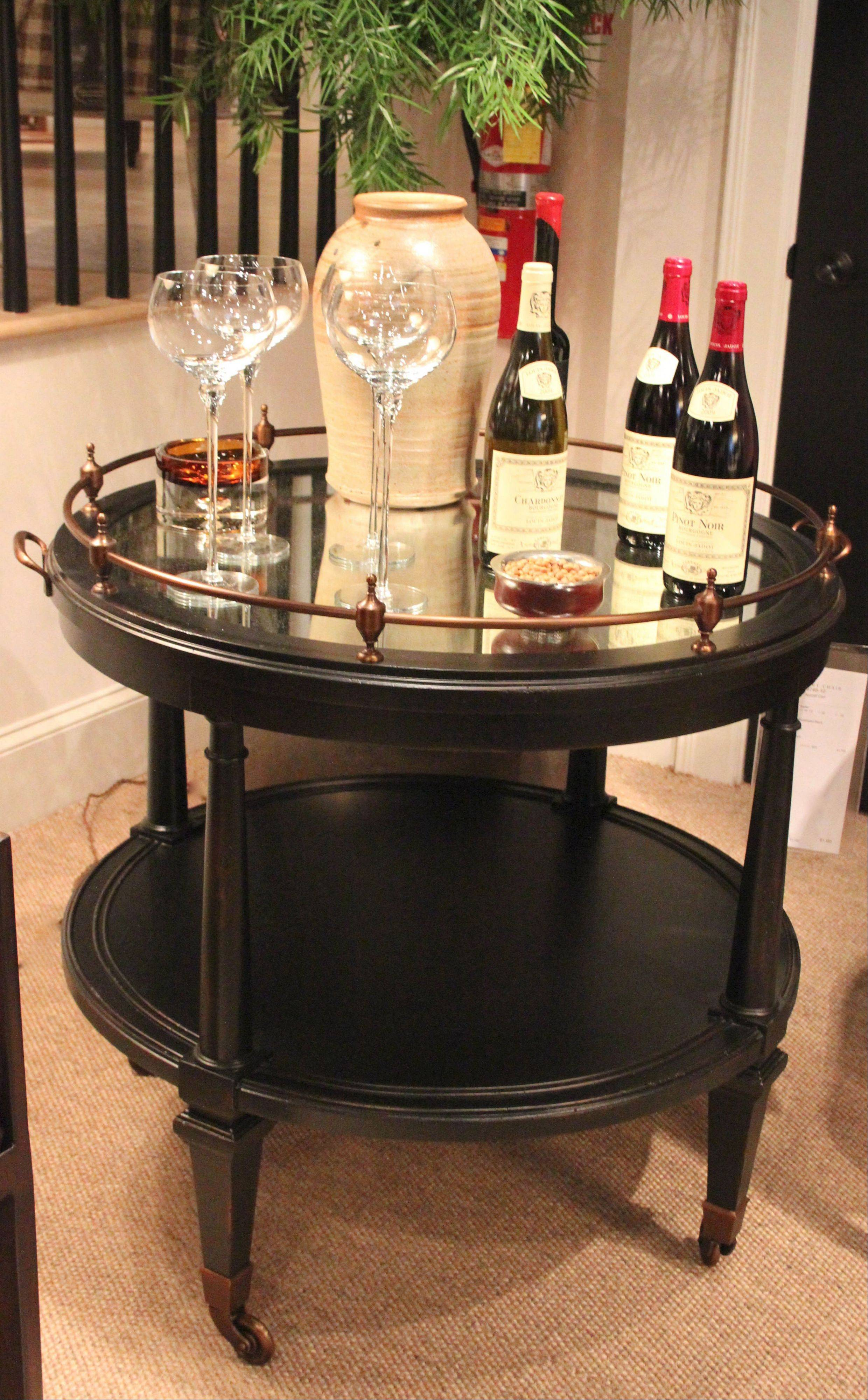 A rolling Aperitif Bar Cart by Hickory Chair has a antique-looking, mirrored tray top with brass and a black finish.