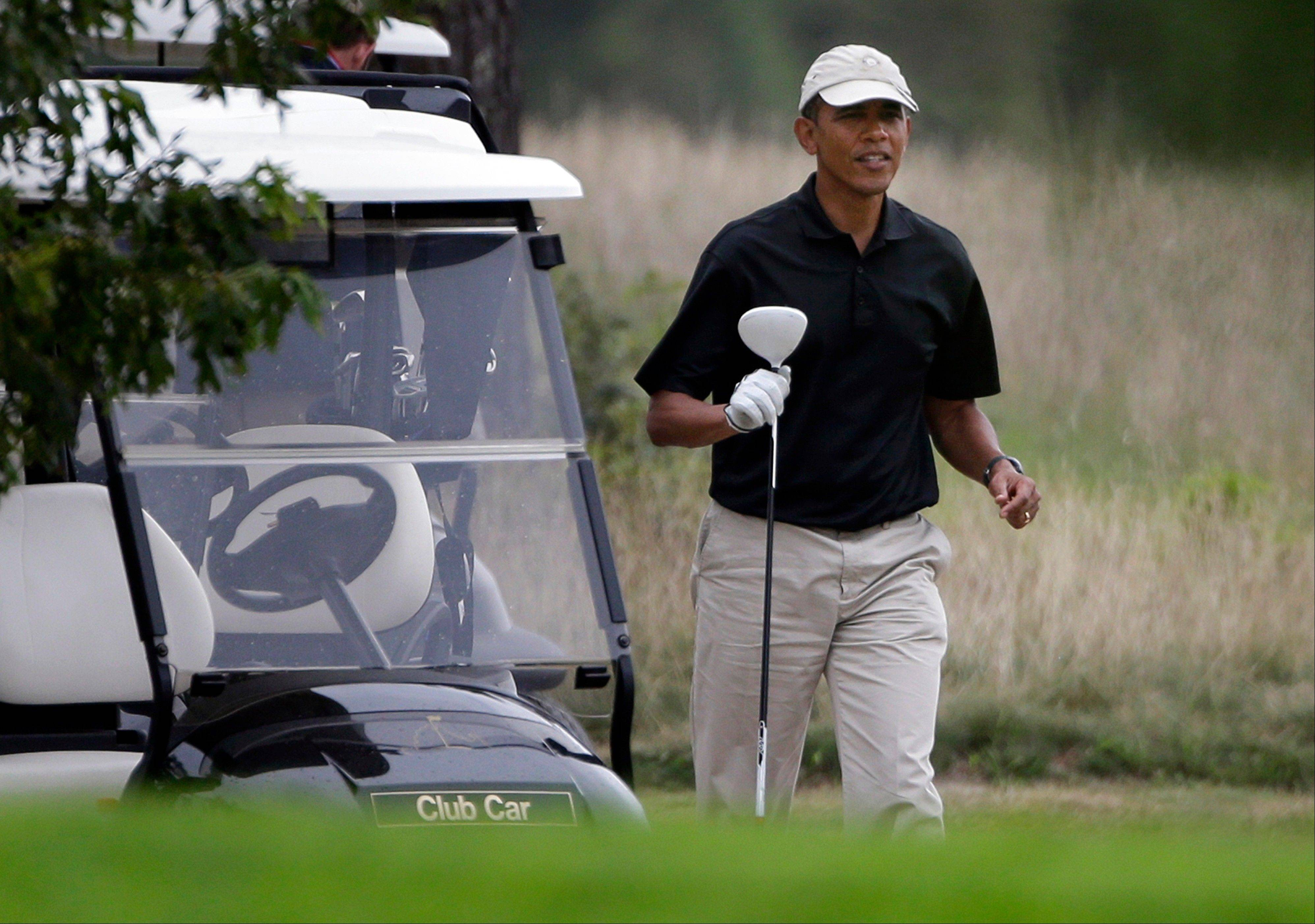 President Barack Obama prepares to tee off while golfing at Vineyard Golf Club in Edgartown, Mass., on the island of Martha's Vineyard Sunday.