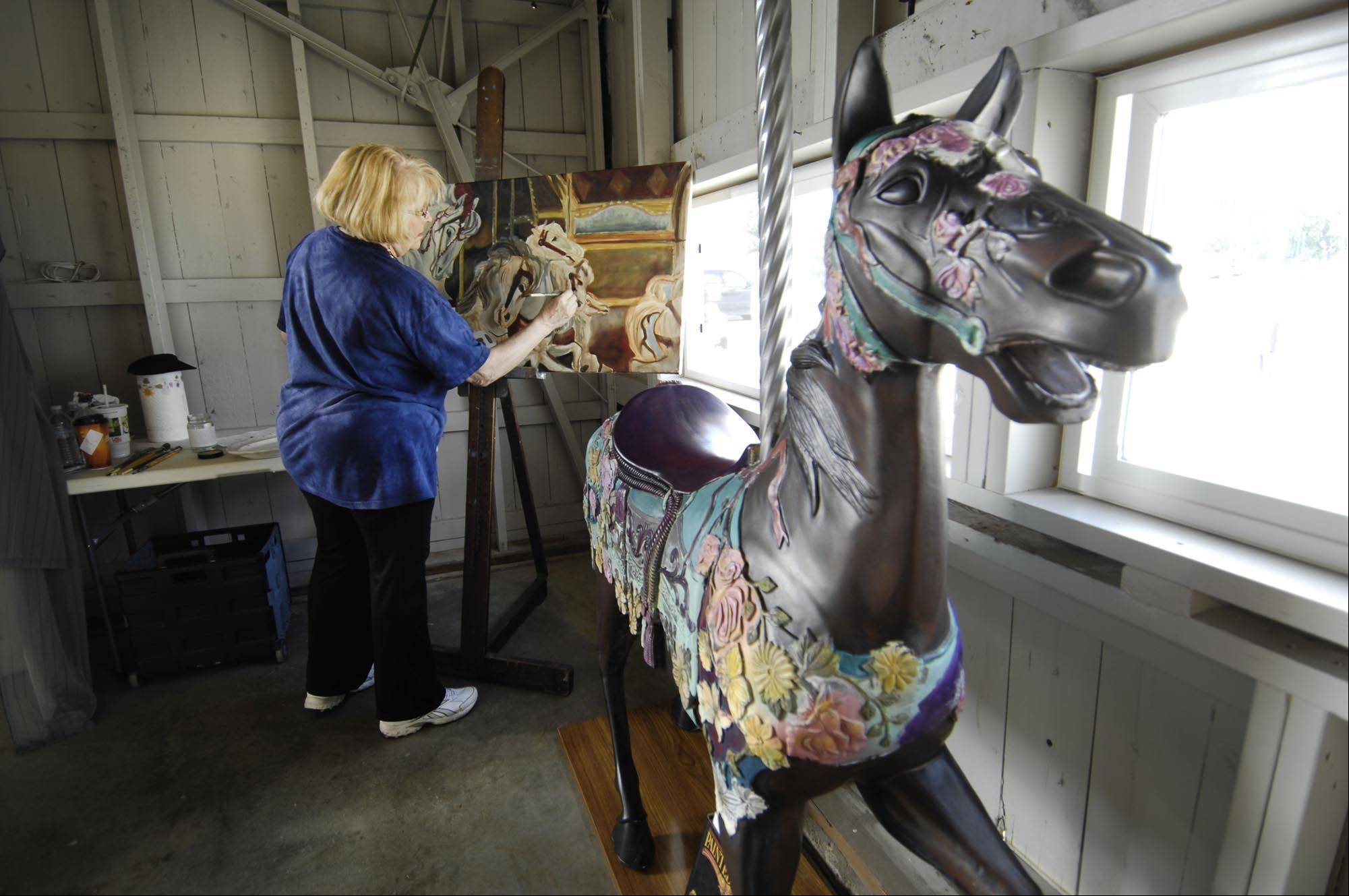 "St. Charles artist Peggy Sue Seehafer paints with oil Sunday during The Festival of the Horse and Drum at the Kane County Fairgrounds. In the foreground is a carousel horse. She was one of several artists on display in a Next Gallery exhibit called ""a horse of a different color"" in one of the barns."