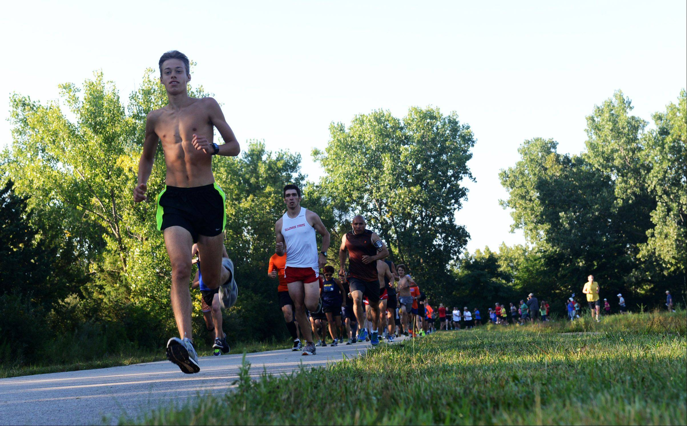 Corey Albrecht, 17, of Algonquin, leads the pack of runners at the Inaugural Raceway 5K Fun Run at Raceway woods in Carpentersville.