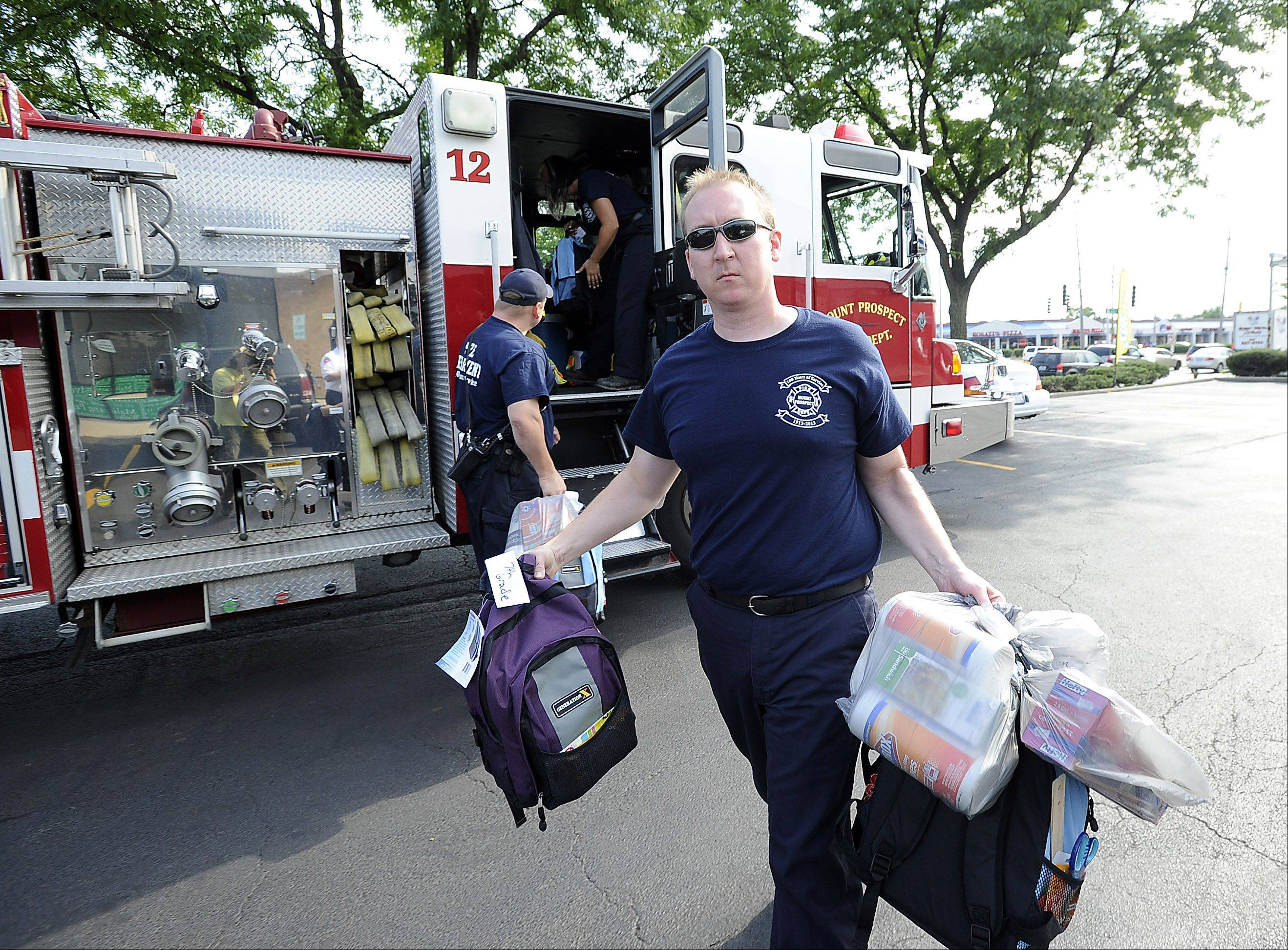 Brad Bocox, firefighter/paramedic for the Mt. Prospect Fire Department, carries backpacks and school supplies to be distributed to families in need, to The Community Connections Center in Mt. Prospect.