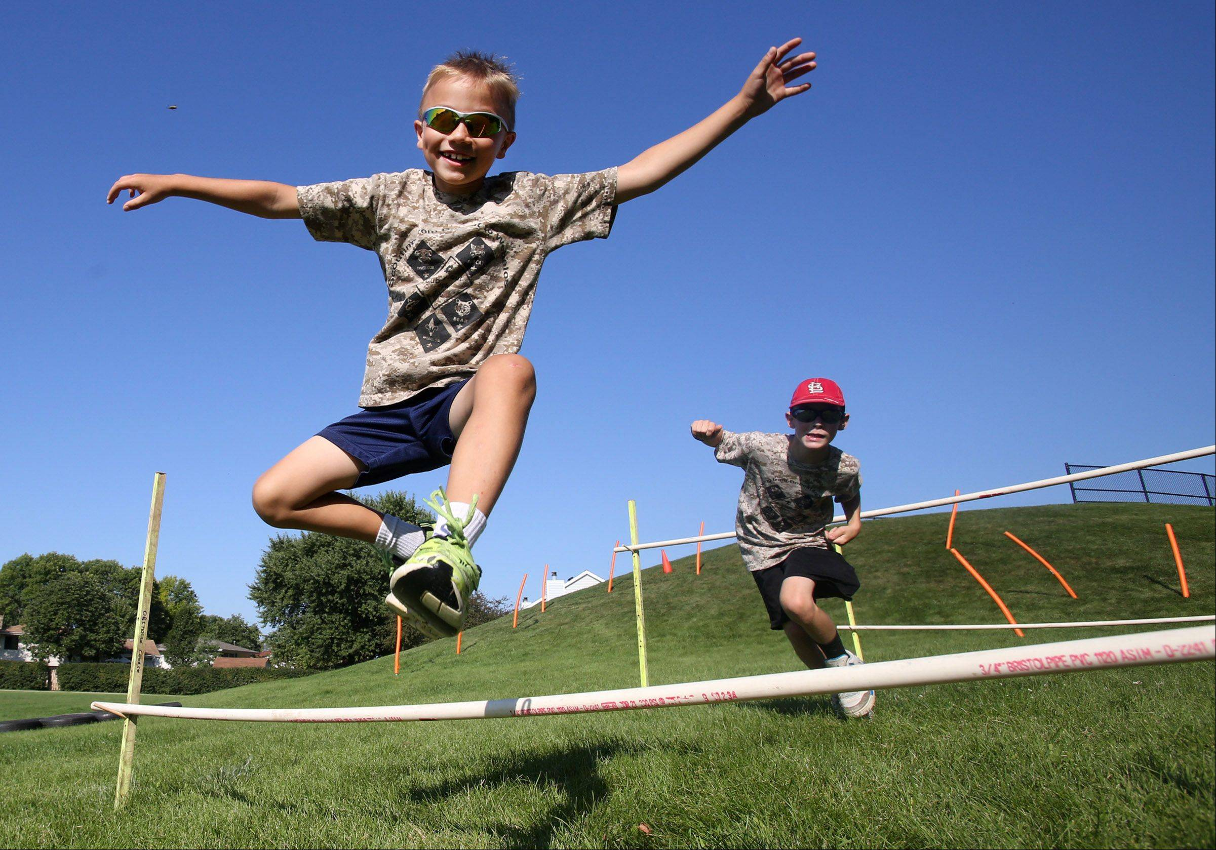John French, 8, followed by Patrick Ortwerth, 10, both of Schaumburg, with Cub Scout Pack 100, leap over a pole on an obstacle course during the 2013 Cub Scout Pathfinder Summer Games held by All Boy Scouts and Pathfinder District of Northwest Suburban Council at Meineke Park in Schaumburg on Saturday.