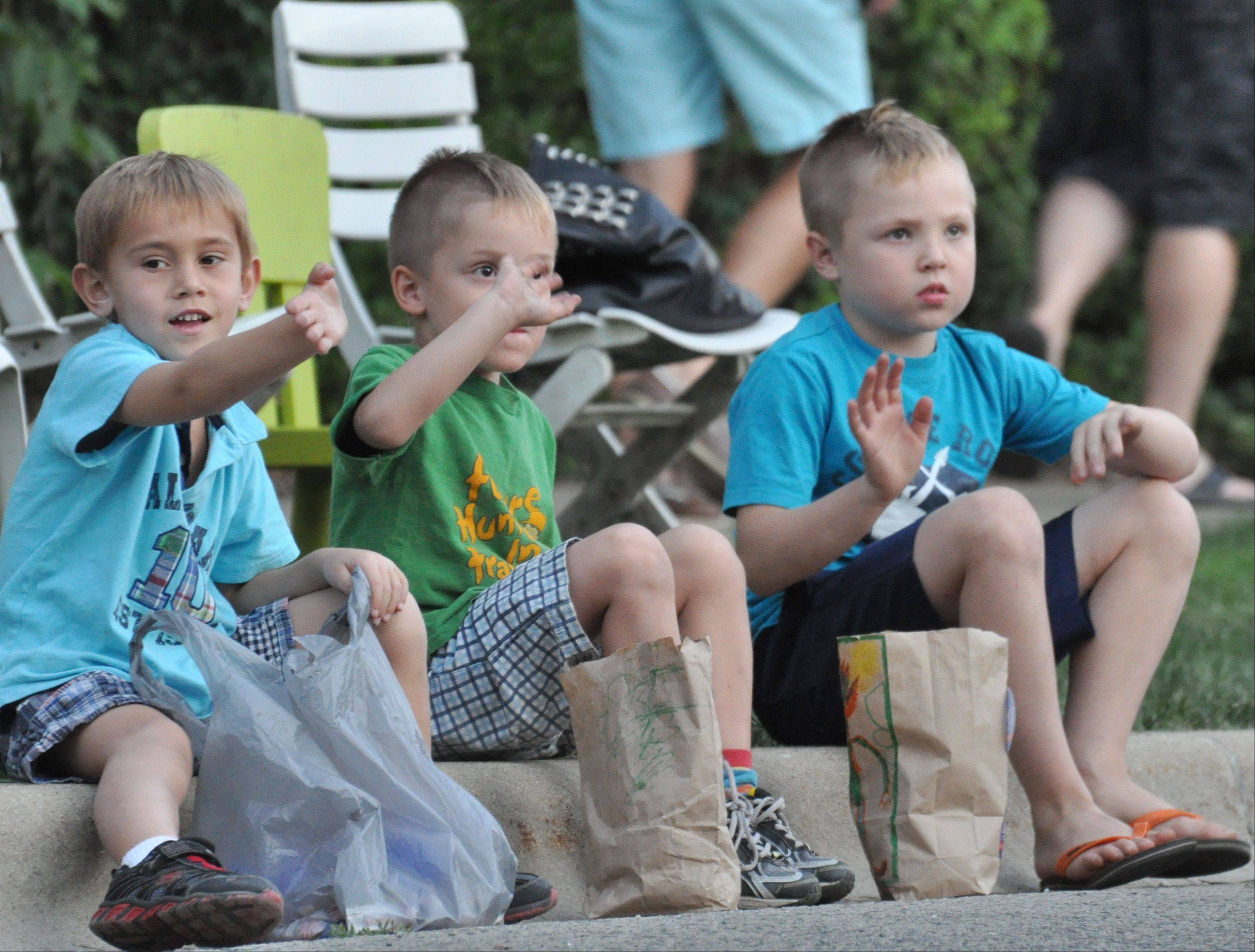 From left, Vince Fenzel, 5, Hunter Bremer, 5, and Christian Bremer, 7, wave at a float during the Summer Days parade in Grayslake Saturday.