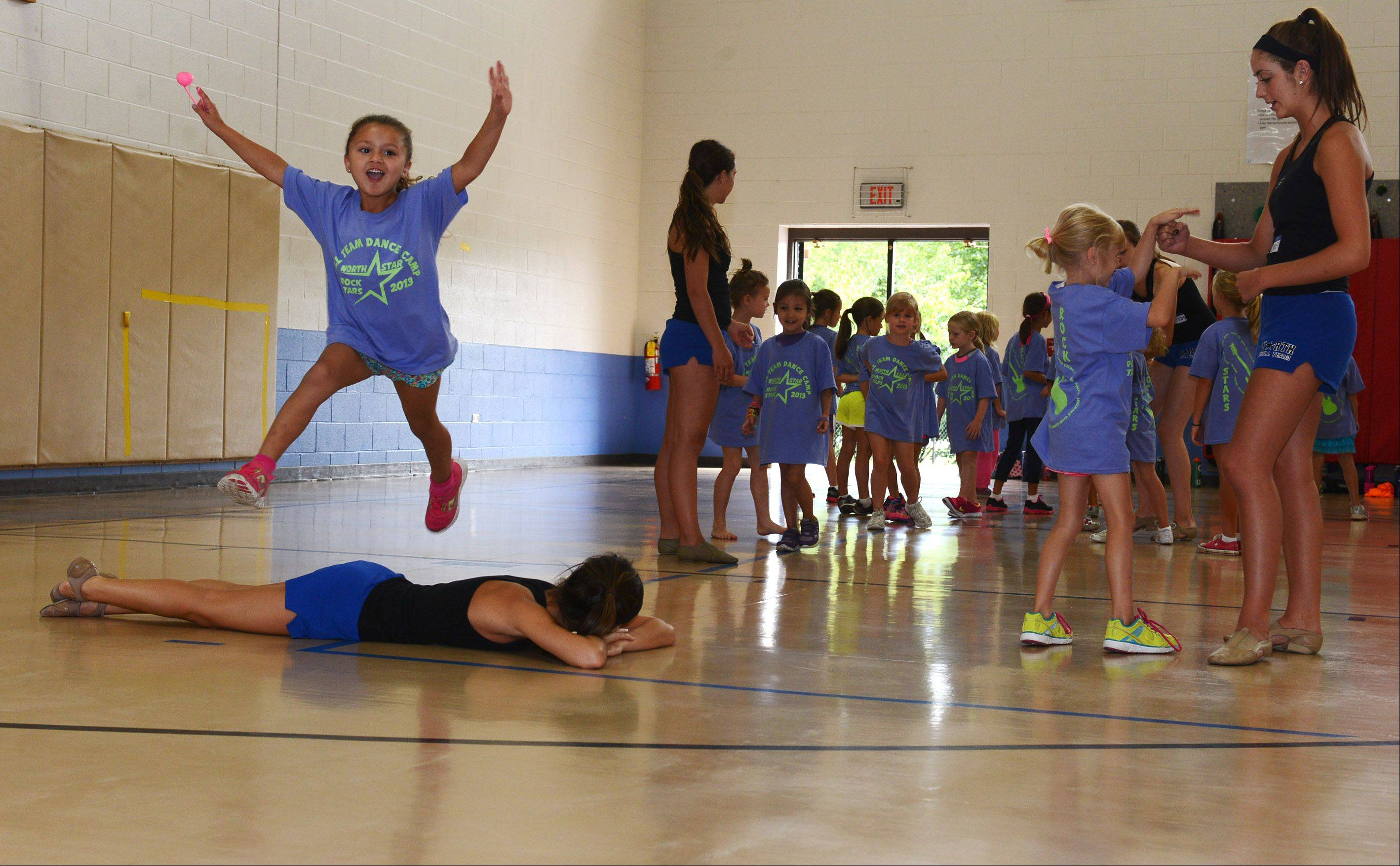 Ava Karoumi, 6, takes a flying leap over one of the North Star Drill Team members, while the rest of her classmates wait for their turn Monday during the 14th annual North Star Dance Clinic at Bell-Graham Elementary School in St. Charles. Girls learned sideline and dance routines, which they will perform at the North Star Football Black and Blue Scrimmage on August 23.