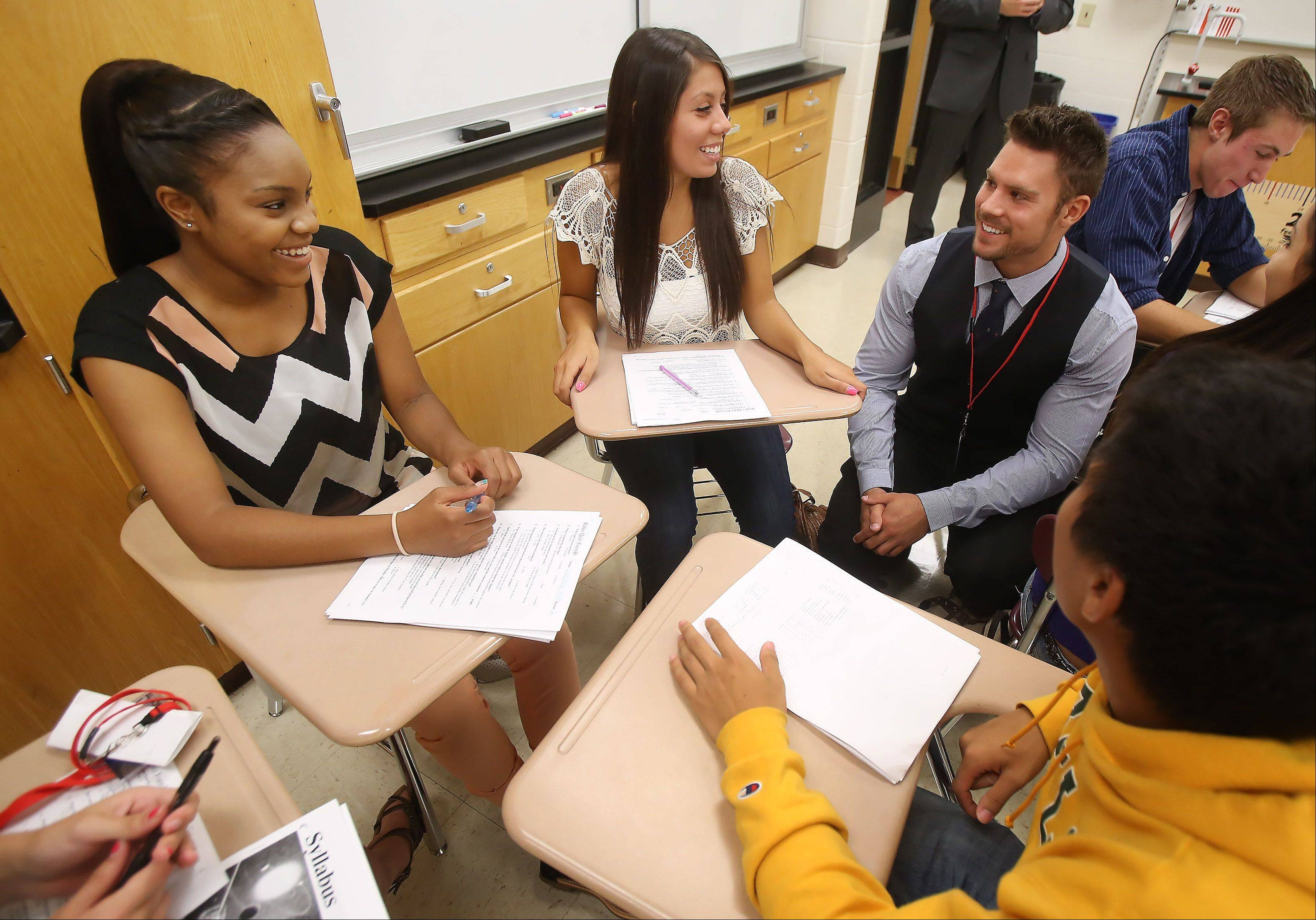 "Juniors Desiree Moreno, left, and Dana Nozime, talk to history teacher Sean Golden as they get to know each other during the first day of classes at Grant High School Wednesday in Fox Lake. ""It is exciting and nerve-racking,"" smiled Golden, a first year teacher. ""It should be a good year."""