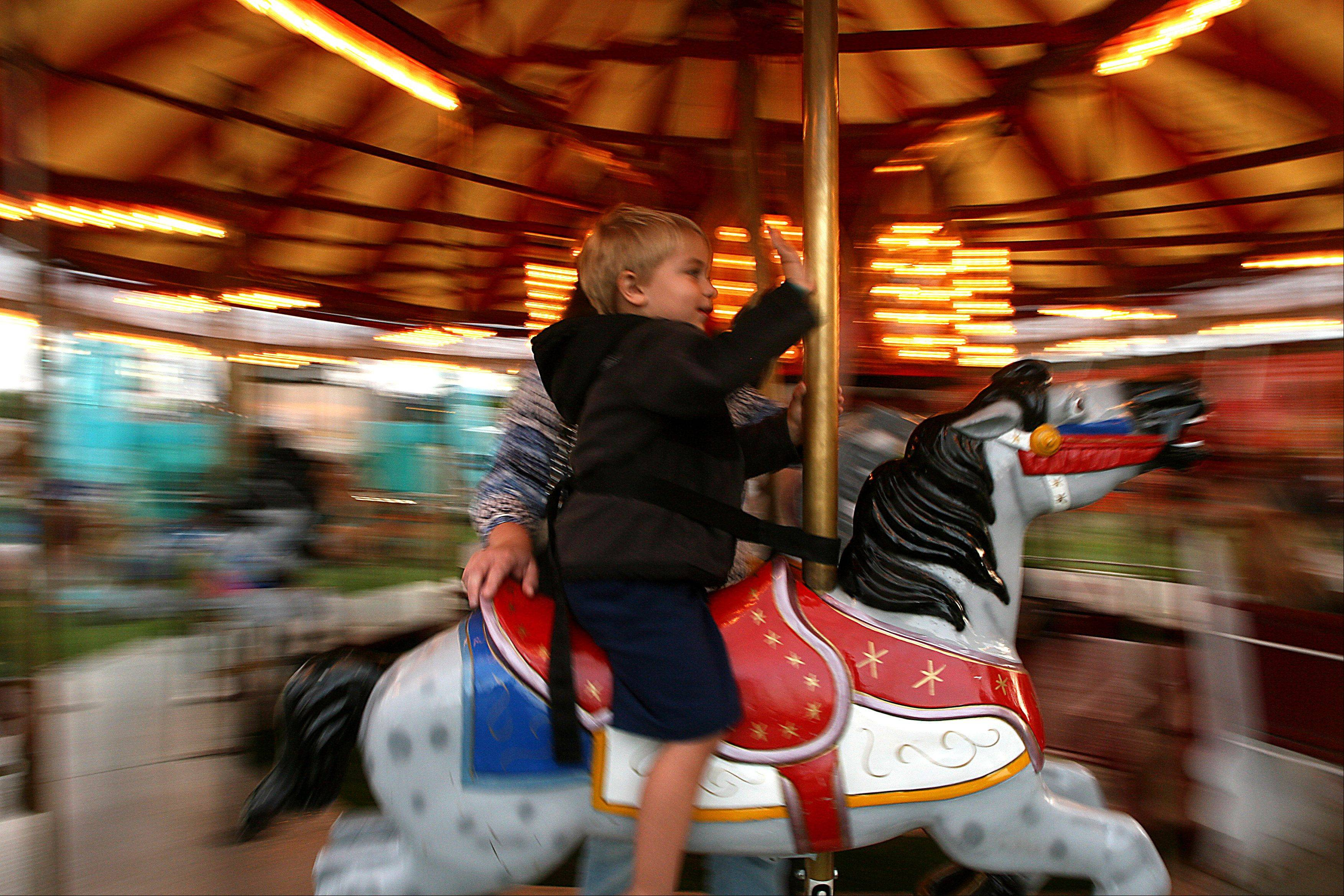 Kian Burkett, 3, waves as he rides the merry-go-round with his mom Heather during South Elgin Riverfest Express festival Thursday night at Panton Mill Park.