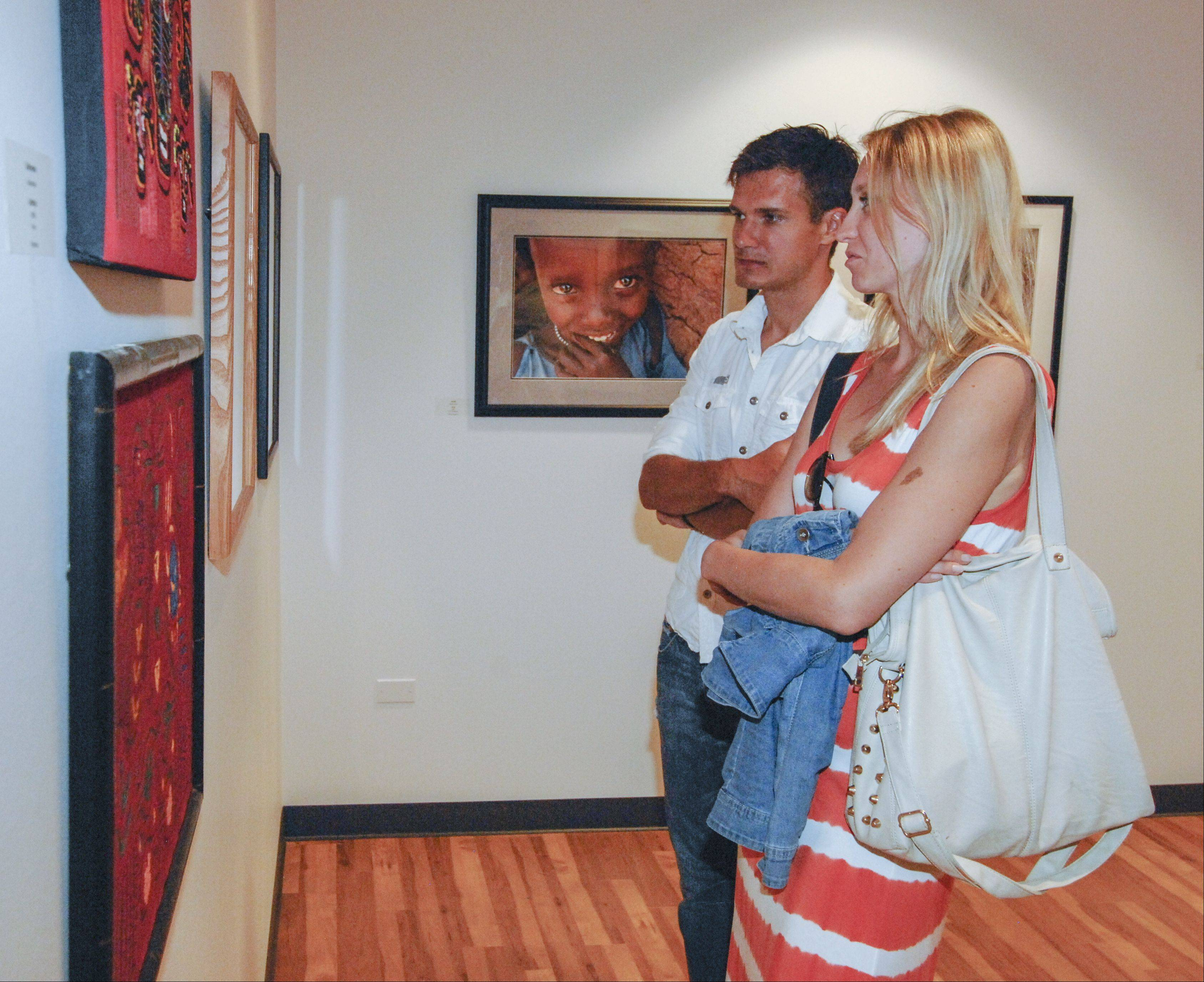 Pawel Pioro and Isavela Mieszcanska, who is a Benedictine University alumni, view the art on display Sunday during the dedication of the new Fr. Michael E. Komechak Art Gallery on the school's Lisle campus.