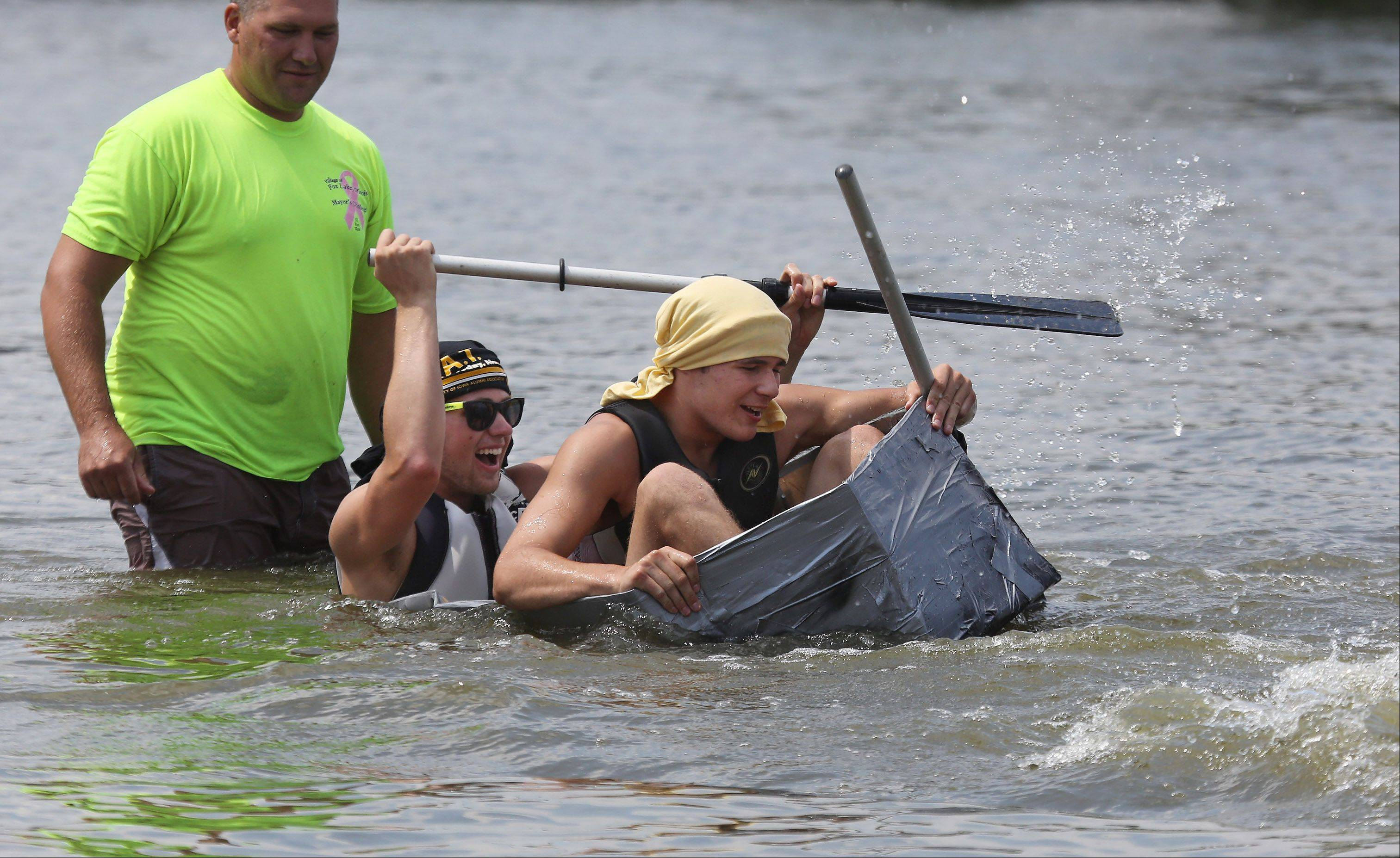 "Thomas Blanchette and Sid Carbone try to paddle as their cardboard boat ""The Friend Ship"" sinks at the start of the 16th Annual Fox Lake Cardboard Cup Regatta Sunday at Lakefront Park. The race offers medals and trophies to contestants who were limited to making boats out of cardboard, duct tape and paint."